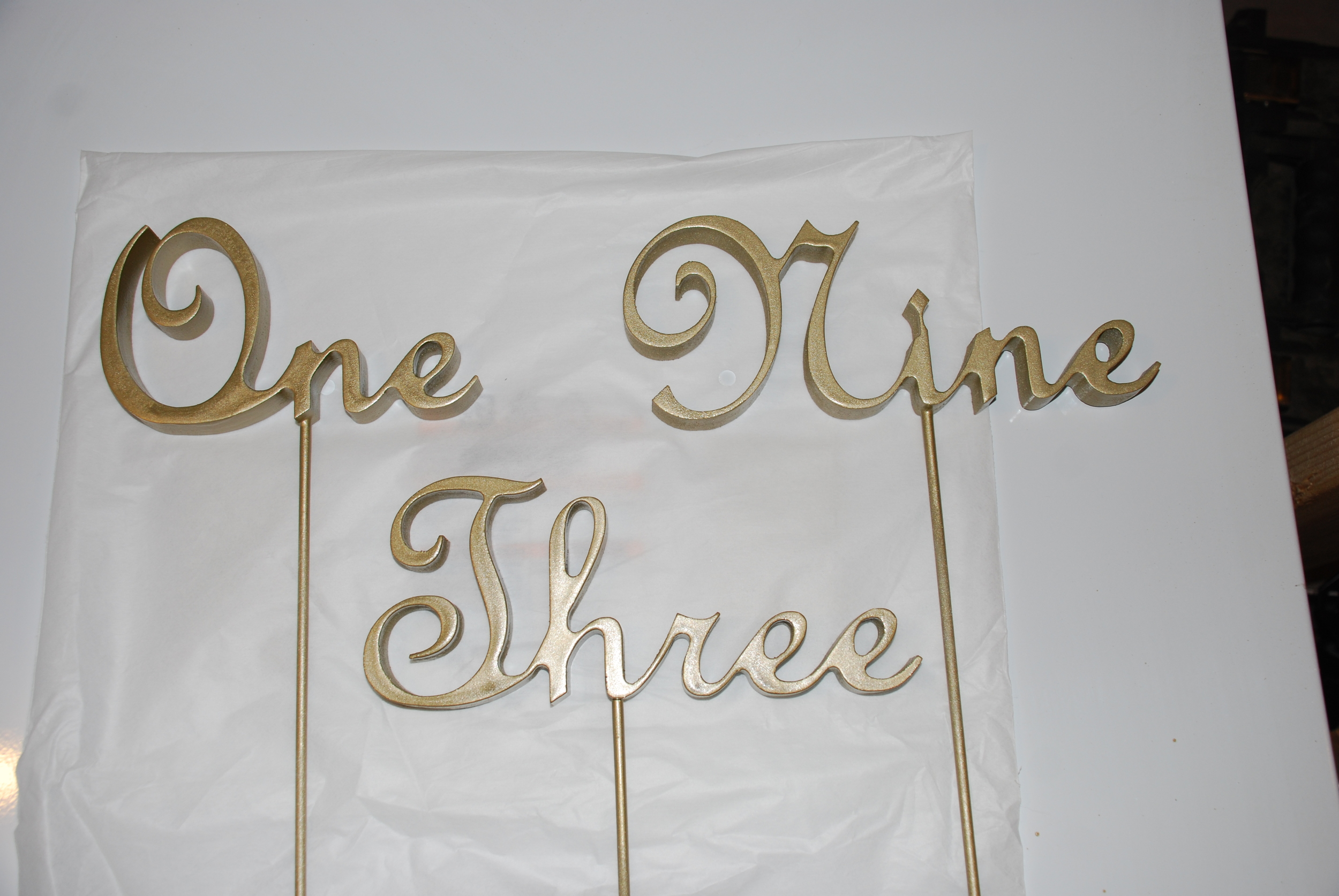 These are destined to be table numbers for a wedding. They were cut from MDF and finished with gold paint.