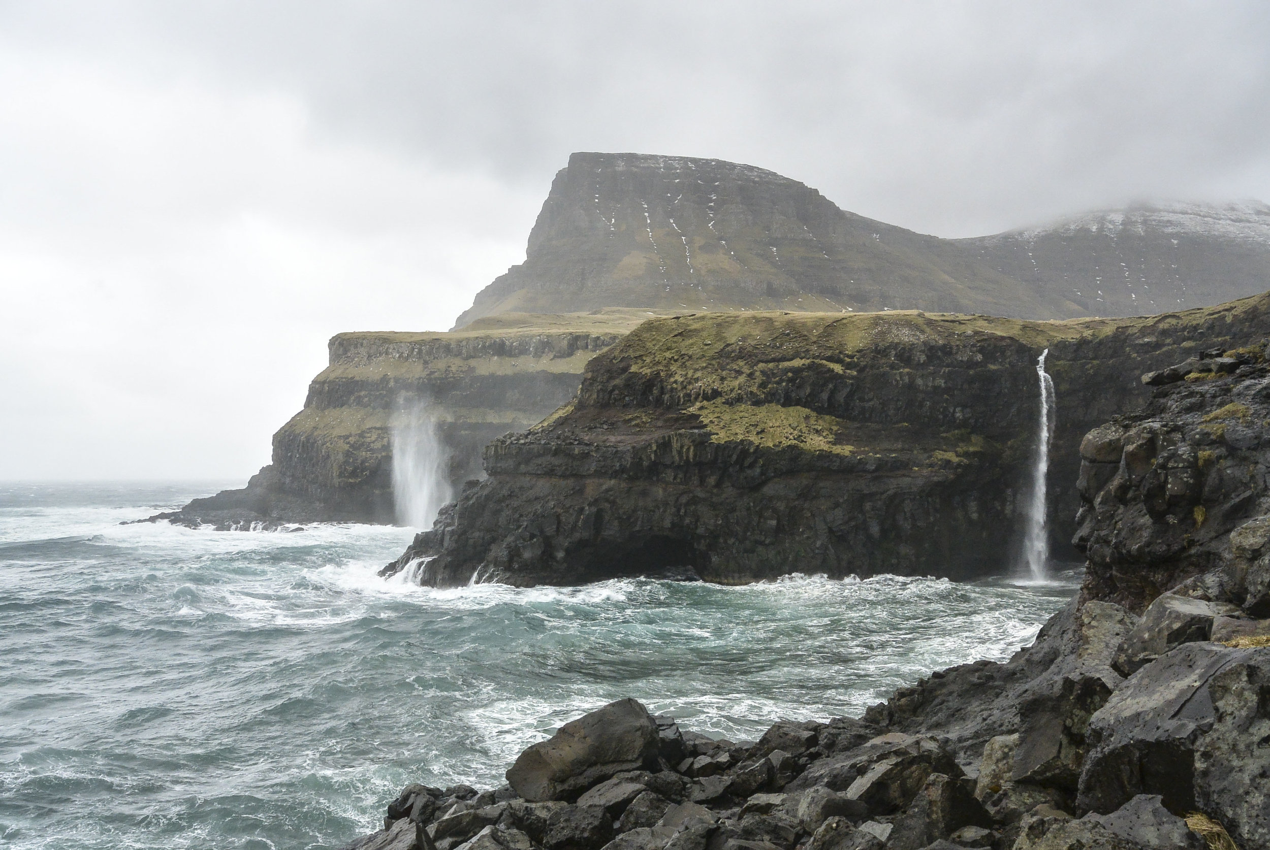 Waves batter the west coast of Vágar on April 18th, 2016, in Gásadalur, Faroe Islands. The small town is a popular destination among photographers, and connected to the rest of the island through a tunnel in the mountainside.