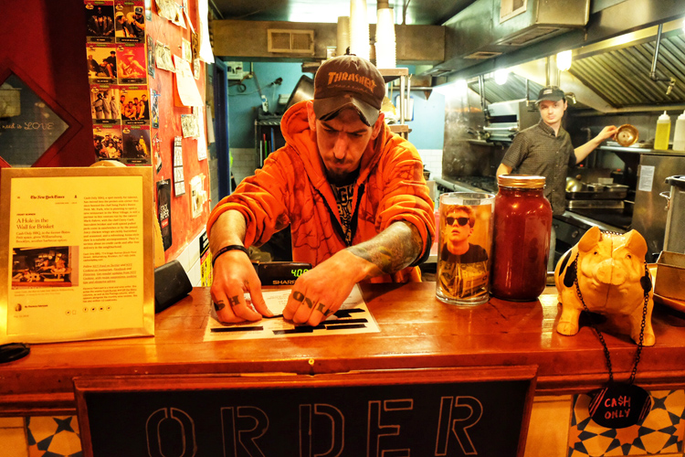 Pitmaster and owner Corey Cash puts tape over sold-out items during the last night Williamsburg's Cash Only BBQ was open.