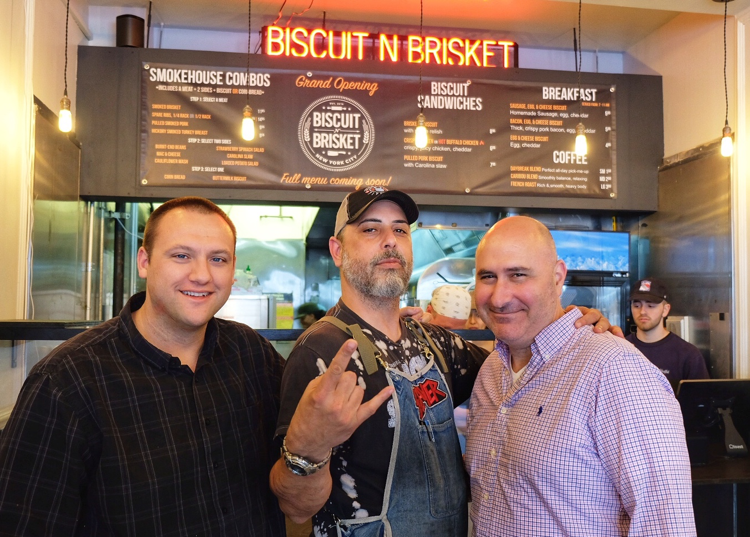 The three business partners behind Biscuit N Brisket pose on opening day, with pitmaster Nestor Laracuente in the center.