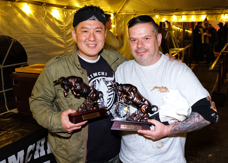 Juicy Lucy BBQ owner Richie Holmes (right) poses with his first place trophy at Brisket King alongside pitmaster Robert Austin Cho of Kimchi Smoke, who won People's Choice.