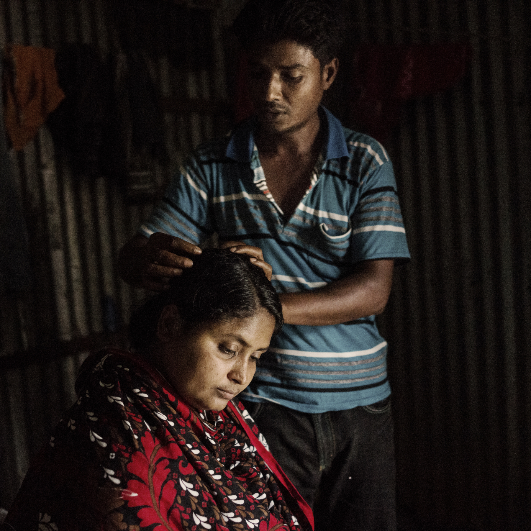 Mominul Islam, husband of Rana Plaza survivor Sharvanu, gently brushes her hair, as he tells the story of finding his wife amongst the chaos.