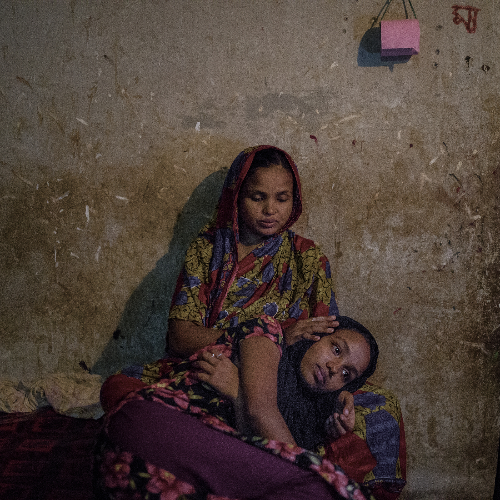 Parvin Begum consoles her daughter Rabeya Khanam, who survived the Rana Plaza collapse but suffers from emotional, mental, and physical trauma