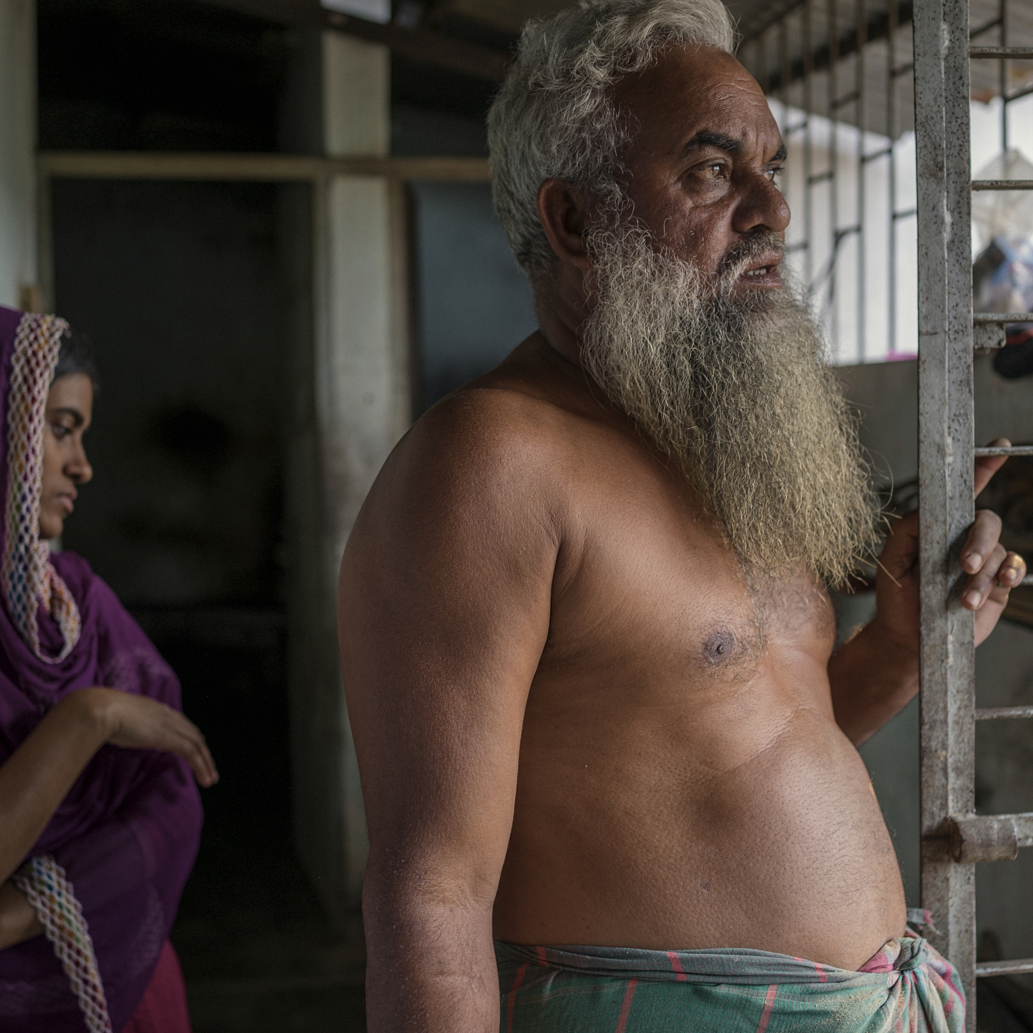 Toslim Mulla, a distant relative of Taslima, looks blankly at the window through which Rana Plaza could be viewed from their house, and gives an account of the disaster.