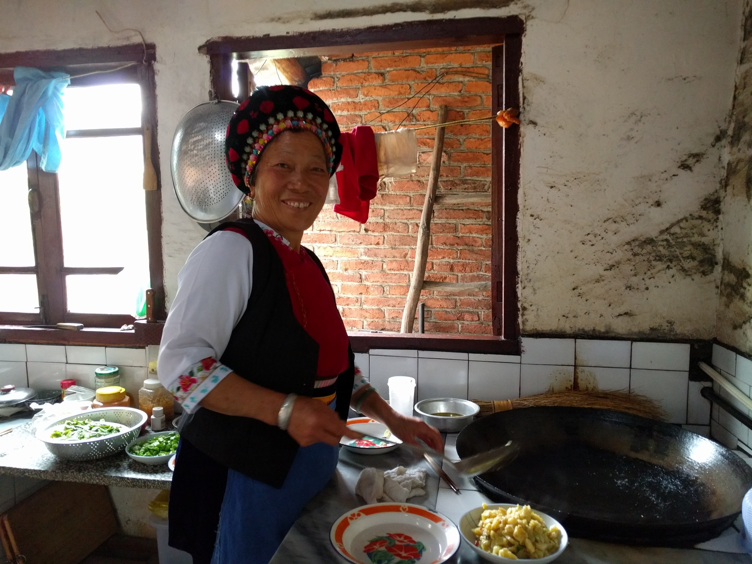 Yang Mama cooking our fresh market veggies in her own kitchen. And yes, the Bai women wear this headdress and outfit in daily life—it's not just for tourists.