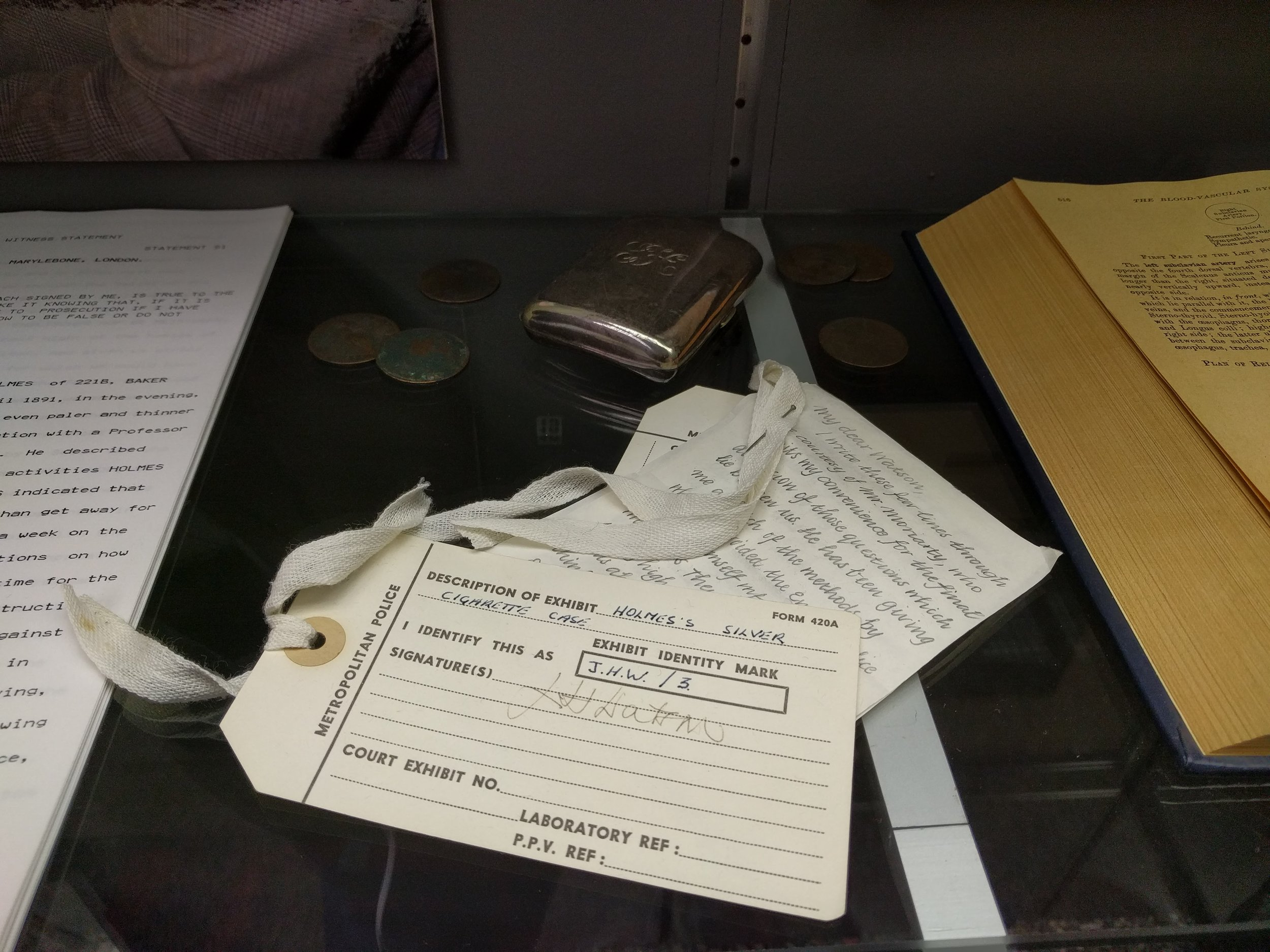 """The rest of the museum is one room of """"artifacts,"""" a collection of real (a Scotland Yard uniform) and imaginary (Sherlock's silver cigarette case and """"in case I die"""" note that he left for Watson on the ledge of the falls, before he tussled with Moriarty. Those items are tagged as if they were part of a Scotland Yard investigation of that time period—and to the left is an imagined statement that would've been given to the police by Watson. So cheesy, so creative, and I loved it all."""