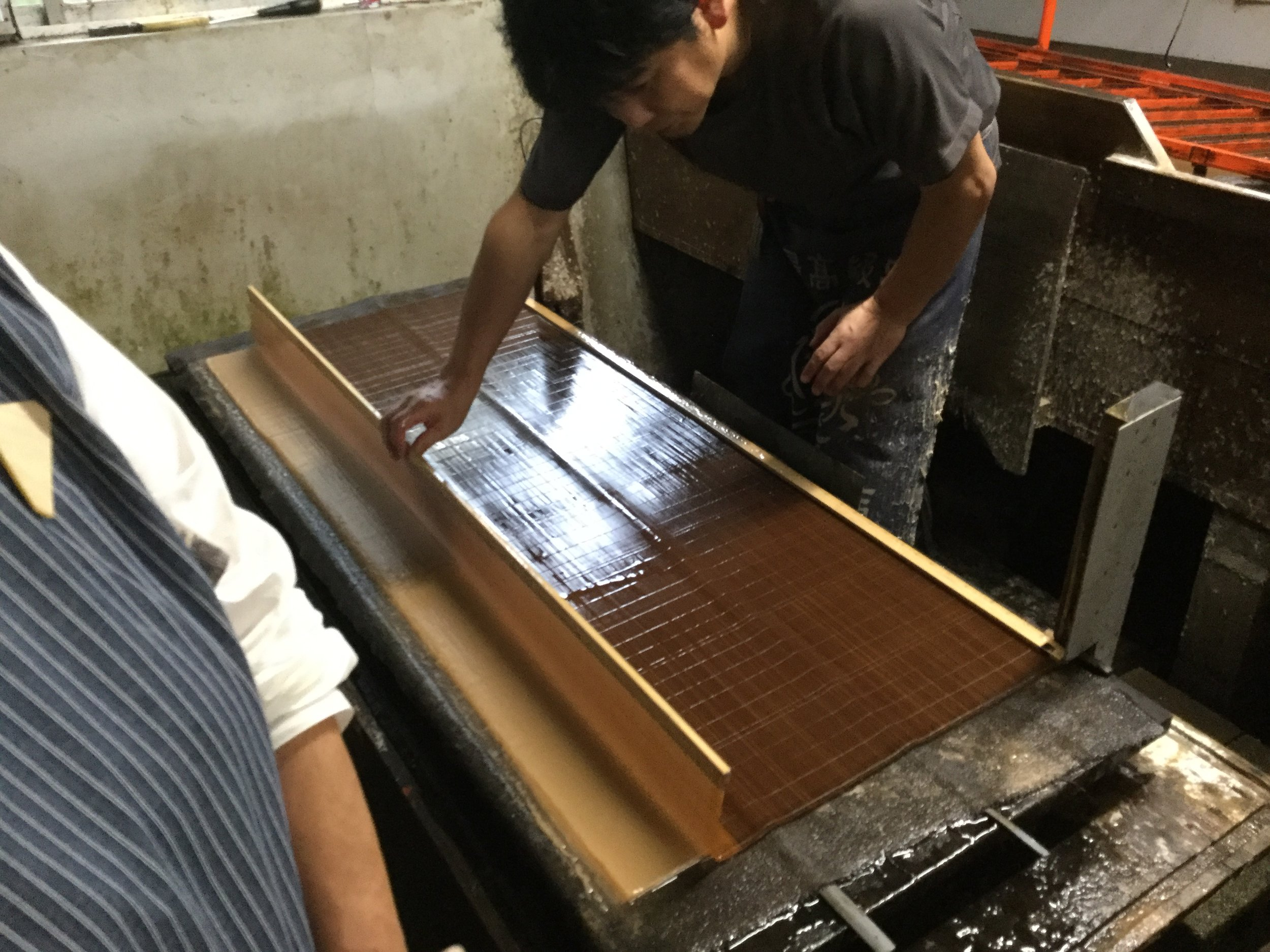 Placing another sheet. There are maybe thirty sheets on the pile. When the pile is full, it gets lifted to a board where it is pressed to drain the water and keep the sheets completely flat. The sheet gets cut in half - the final papers are half the size of the bamboo mat.