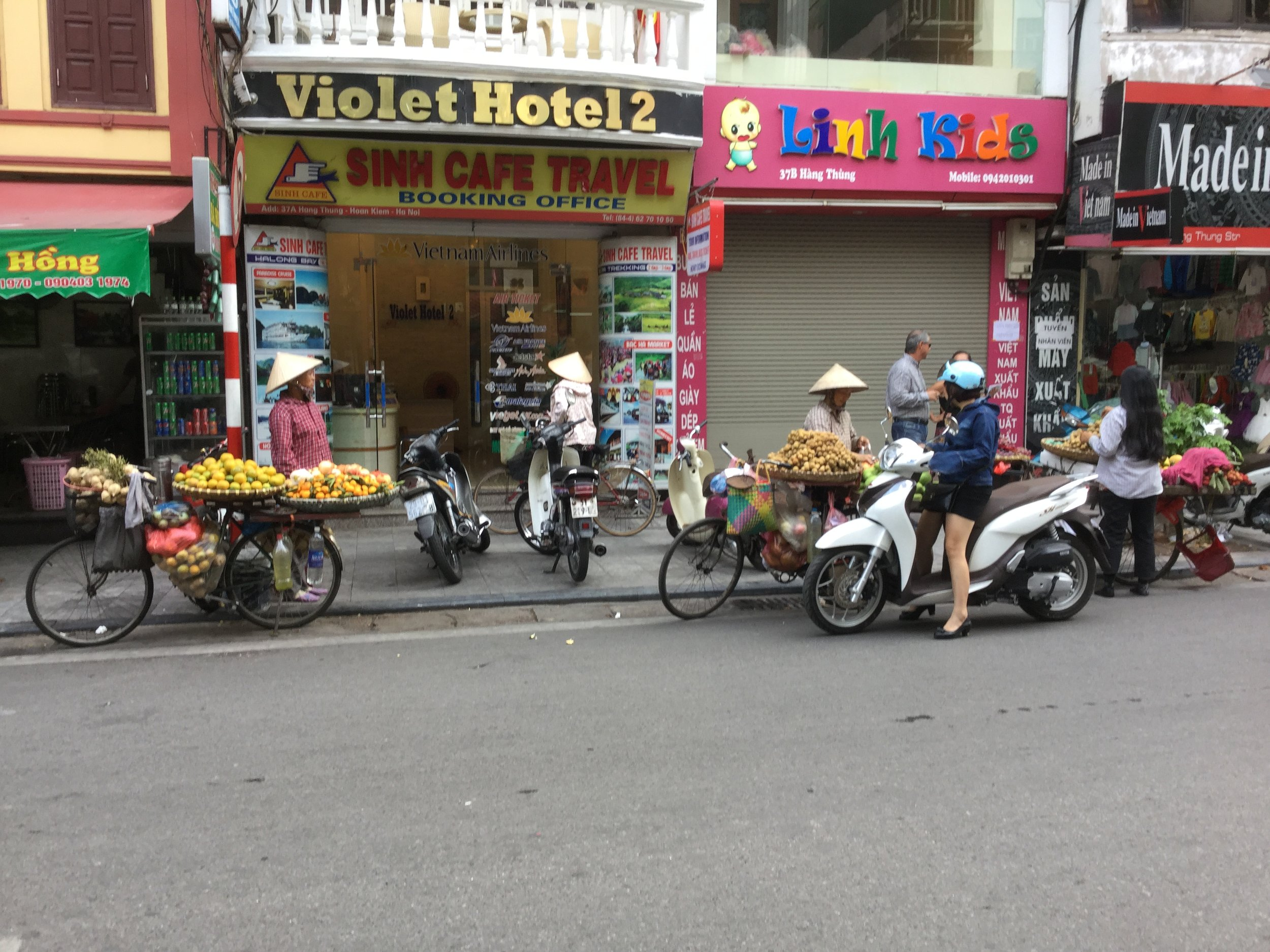 Stores in the street and stores on a bicycle.