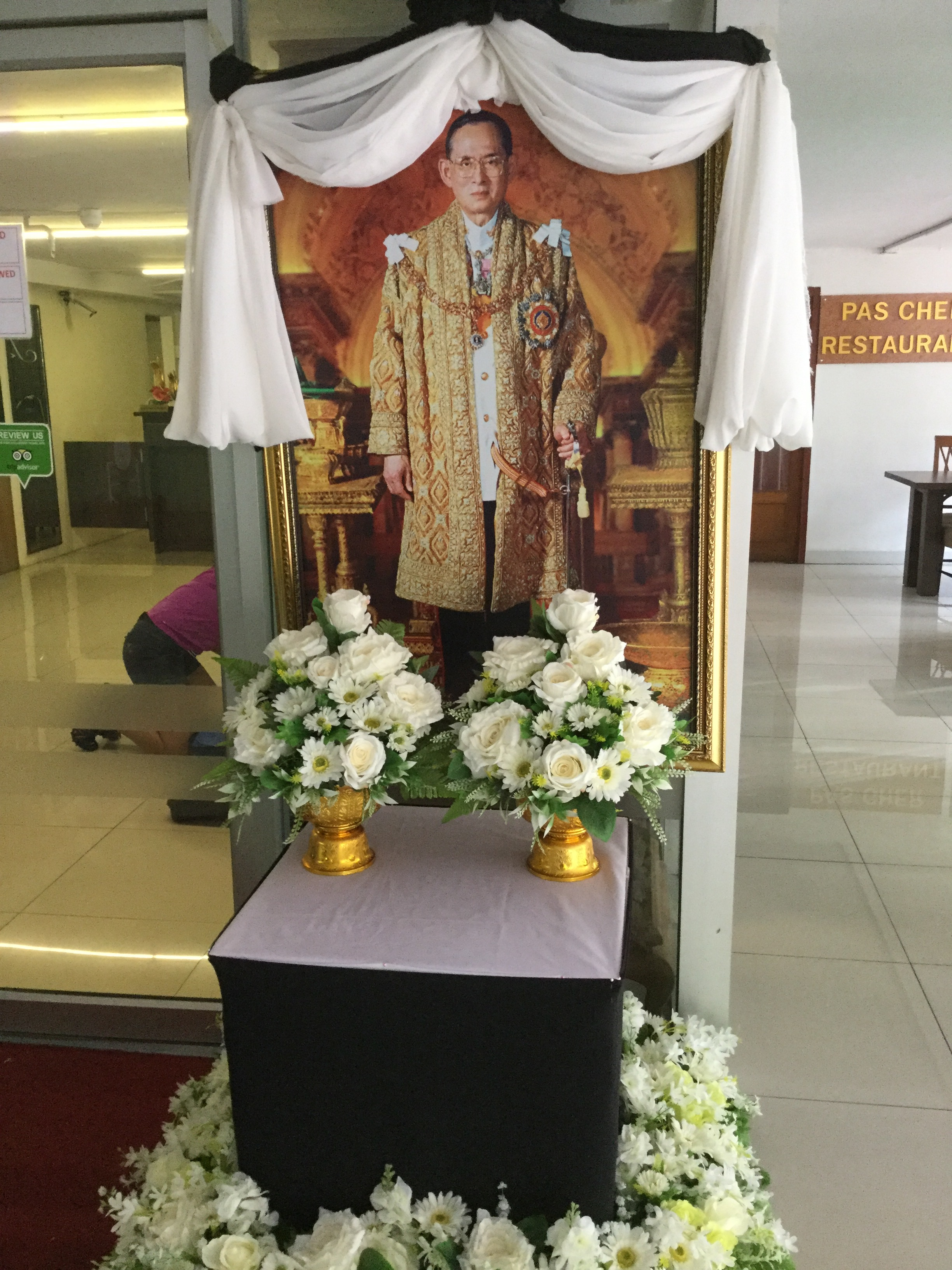 One of the many commemorative images of the King at entry to buildings. Black and white ribbons are everywhere in the City.