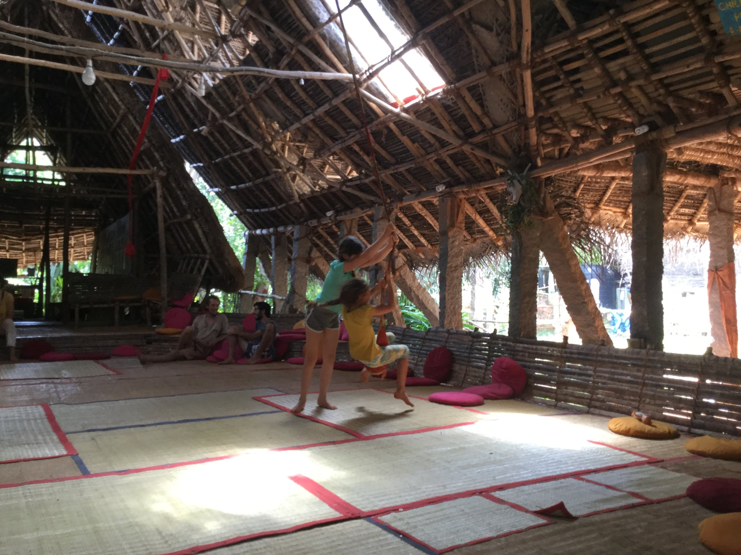 Sadhana Forest main hut. Lili and Shalev are having fun with the ropes.