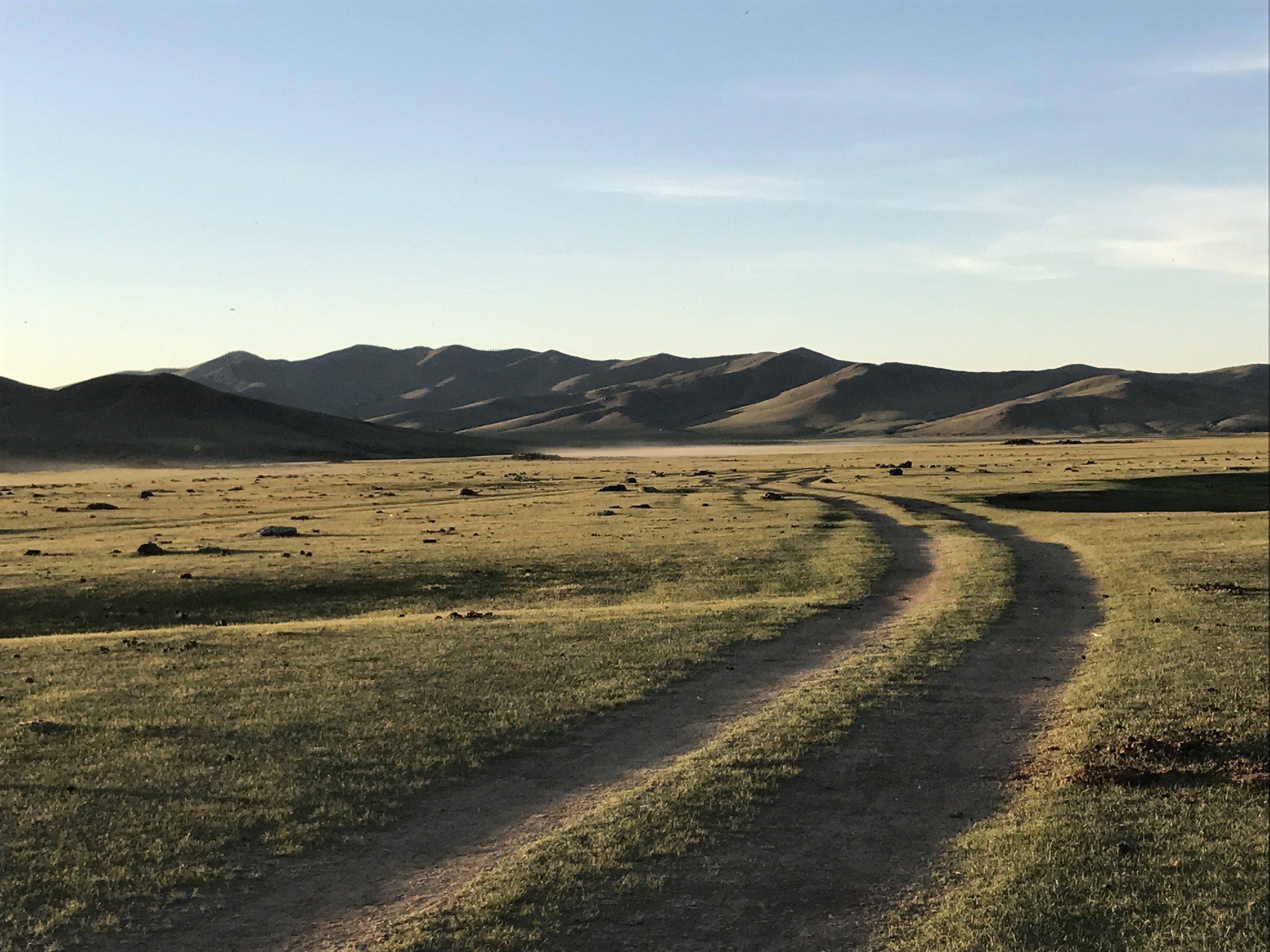 Sunset after a warm day on the steppe. We drove on a road like this through a volcanic rock field for two hours.