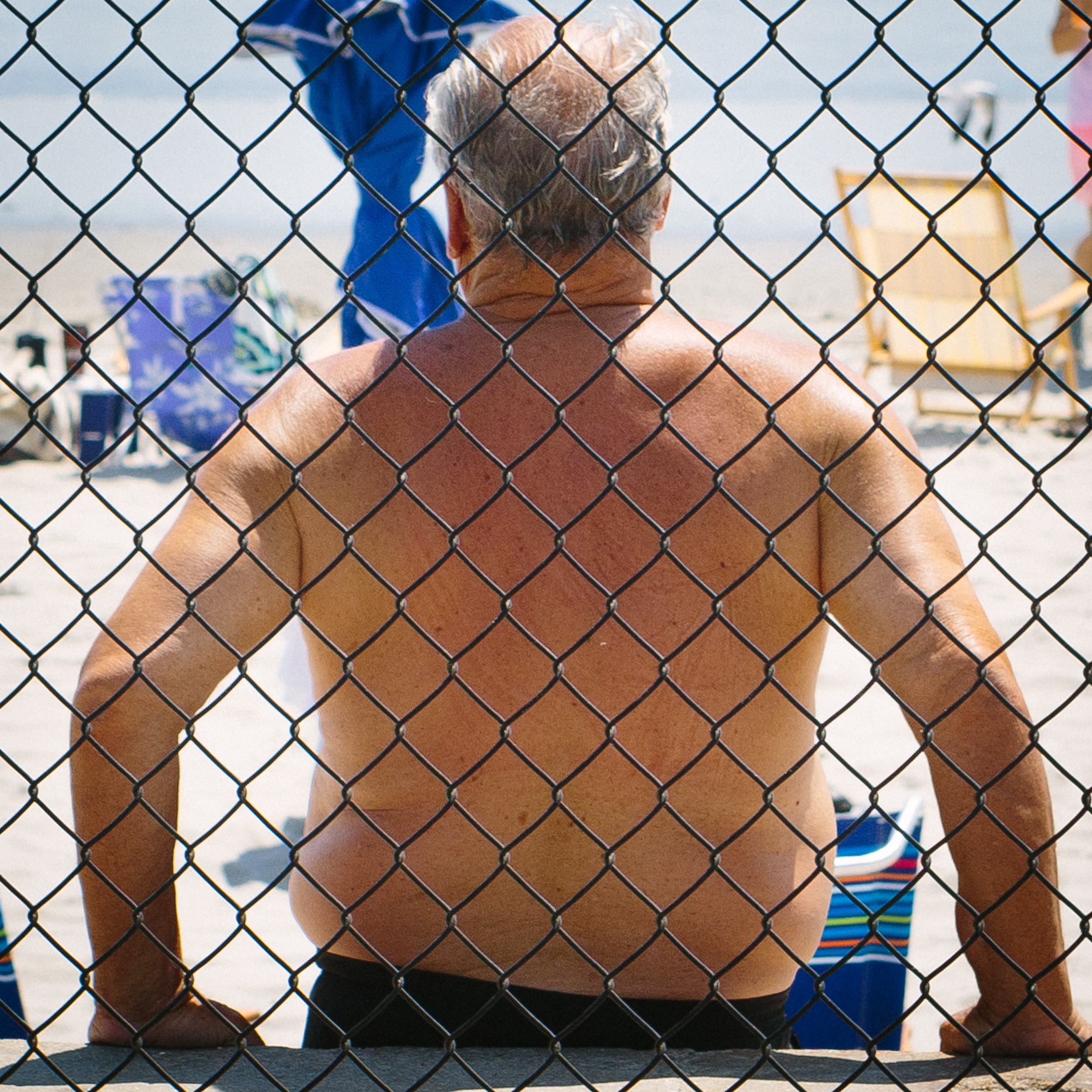 Middle-aged man through chain link fence