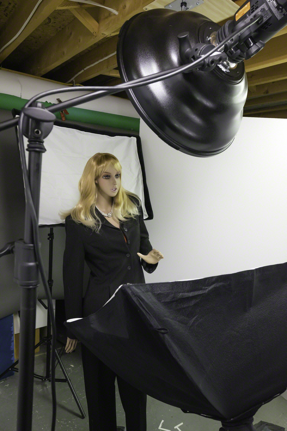 From camera left, this angle gives a clearer view of the positioning of the fill and back light soft boxes. You see particularly that the back light is nearly touching Darla's shoulders. The white panel to the right in this image and to the left in the prior image are v-flats. I use them to simulate the effect of white walls in a small shooting space and to prevent inappropriate reflections from the shelves in the studio.