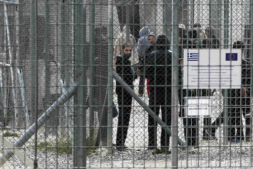 Immigrants stand behind a fence at a detention centre in the Amygdaleza suburb of western Athens February 14, 2015. REUTERS/ Alkis Konstantinidis