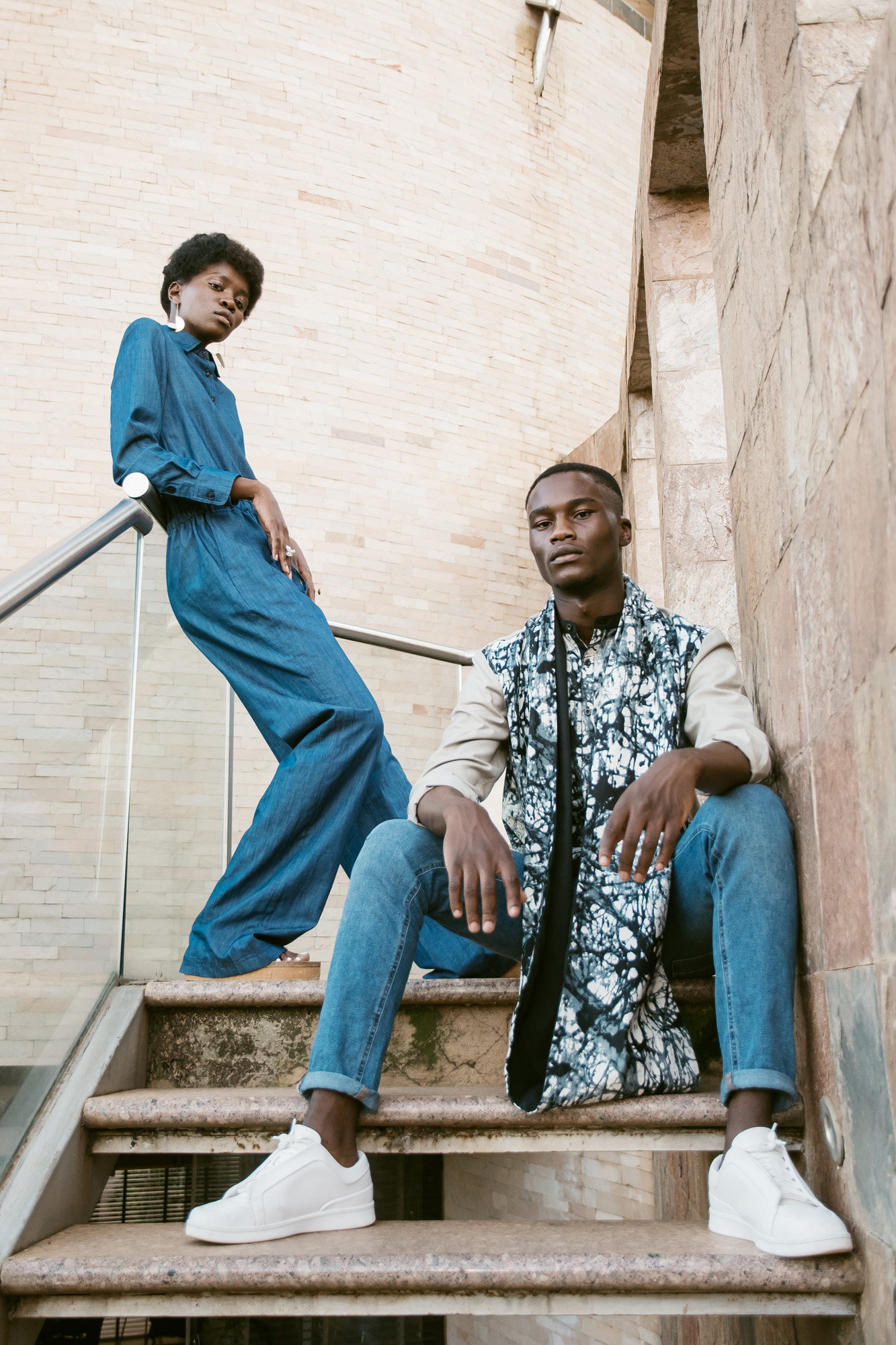 Anita wears Haute Baso jumpsuit, Ami Doshi Shah earrings and rings, I.Am.Isigo sandals. Randy wears House of Tayo shirt and snood, own jeans and trainers