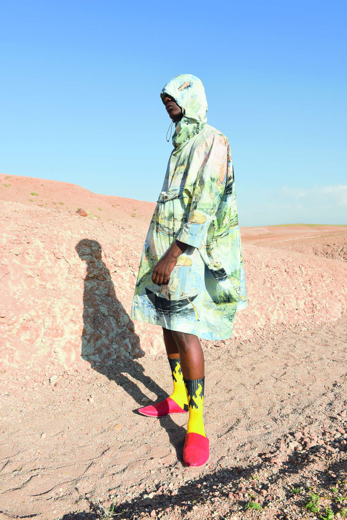 PATRICE wears OFF WHITE poncho, SOUK MEDINA MARRAKECH babouche slippers, WEEKDAY socks.