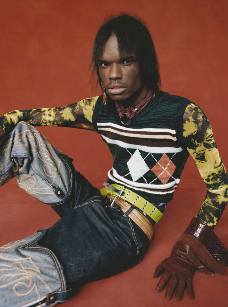 DARIUS wears PREEN LINE jumper, GUCCI gloves, ASAI trousers, FIGURE OF A necklace, DINOSAUR DESIGN earring, vintage top and belts.