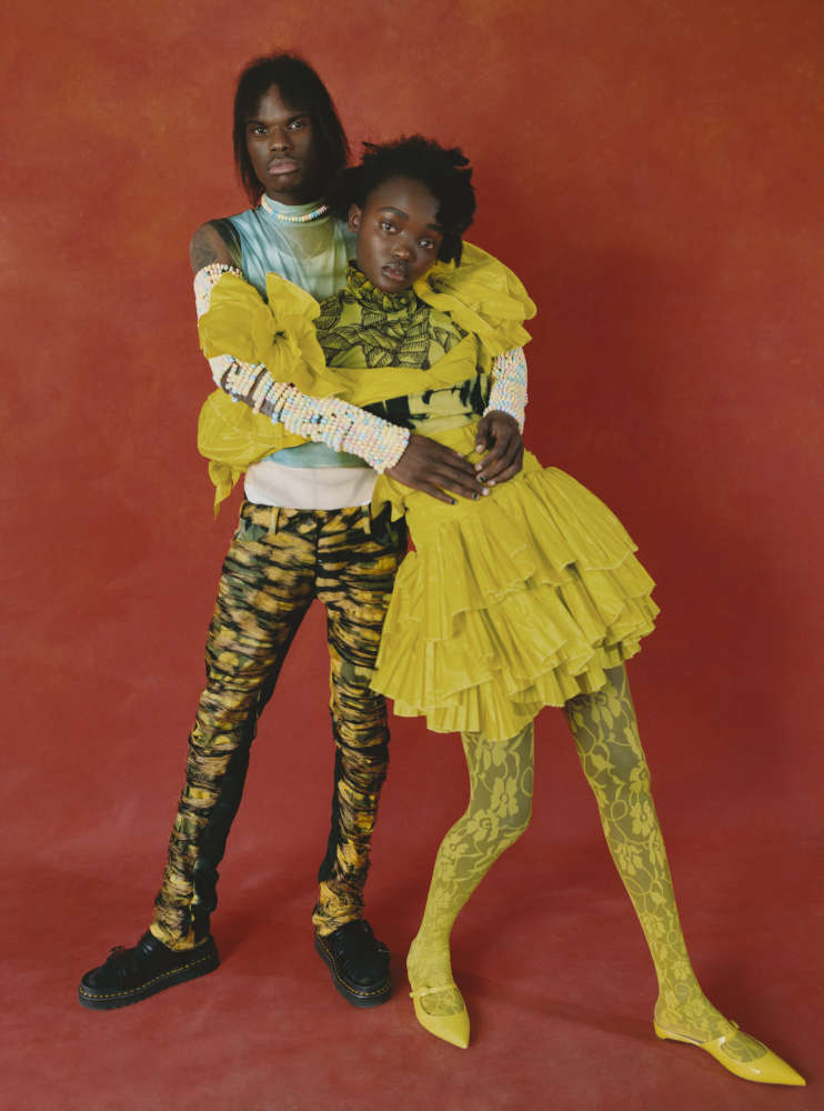 DARIUS wears WOLFORD bodysuit, RIONA TREACY vest, MOWALOLA trousers, DOC MARTENS shoes.    YACINE wears GUCCI dress, PRONOUNCE top, EMILIO CAVALLINI tights, MOWALOLA belt, RUPERT SANDERSON shoes.