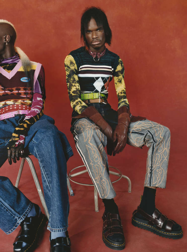 MAGUEYE wears ASAI top, ANGUS CHIANG jumper, AMAZON FASHION trousers, DOC MARTENS shoes, vintage belts.    DARIUS wears PREEN LINE jumper, GUCCI gloves, ASAI trousers, DOC MARTENS shoes, FIGURE OF A necklace, DINOSAUR DESIGNS earrings, vintage top and belts.