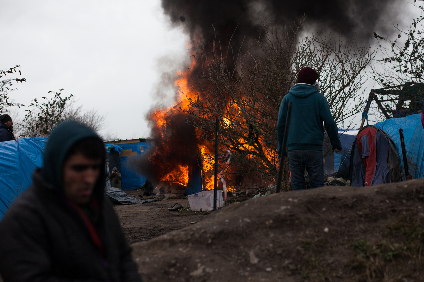 Des migrants mettent feu à certaines habitations avant qu'elles ne soient détruites par les forces de l'ordre.  L'Humanité - 4.03.16