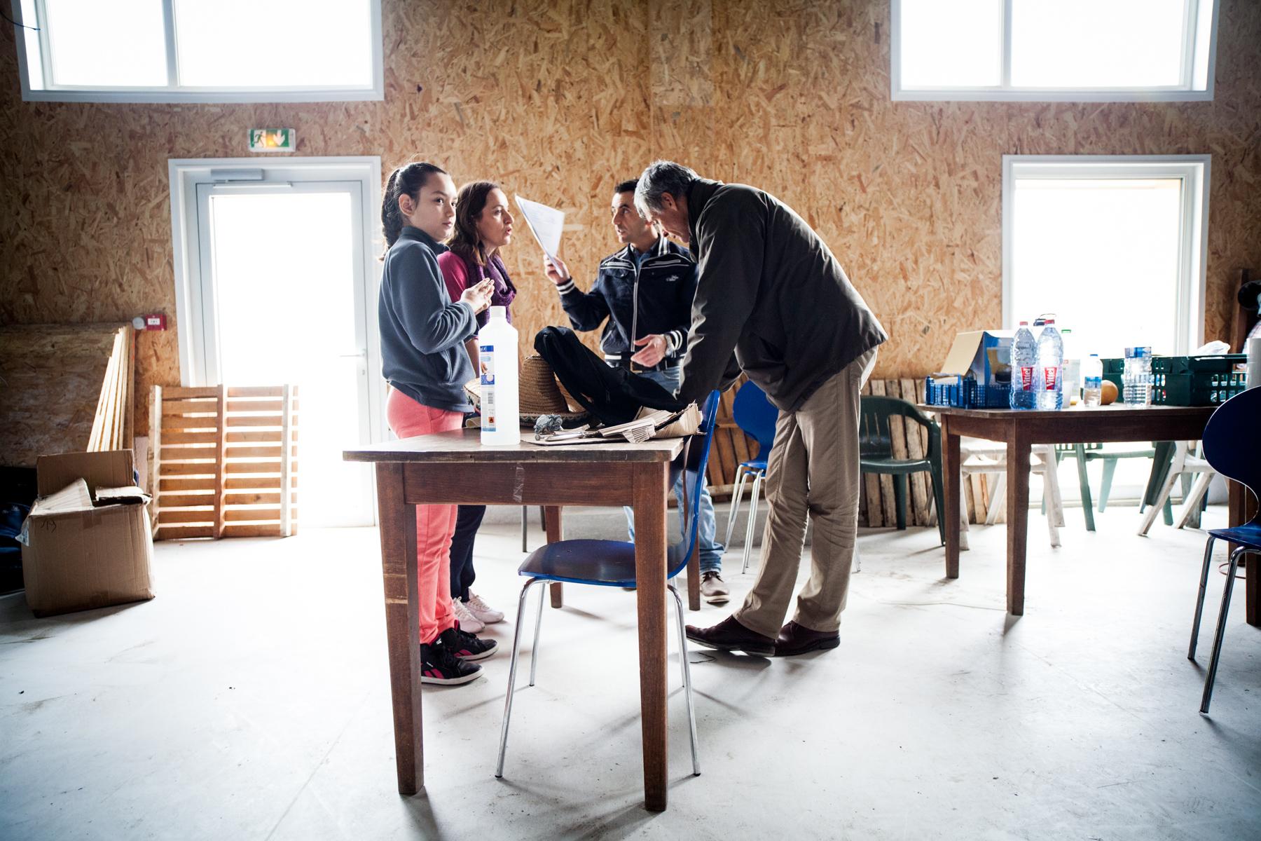 Vincent, du Secours Catholique,prend le temps d'examiner les papiers d'un réfugié et de lui expliquer ce qu'il peut en attendre. Les familles calaisiennes sont là pour en discuter également.  Témoignage Chrétien - 30.10.15