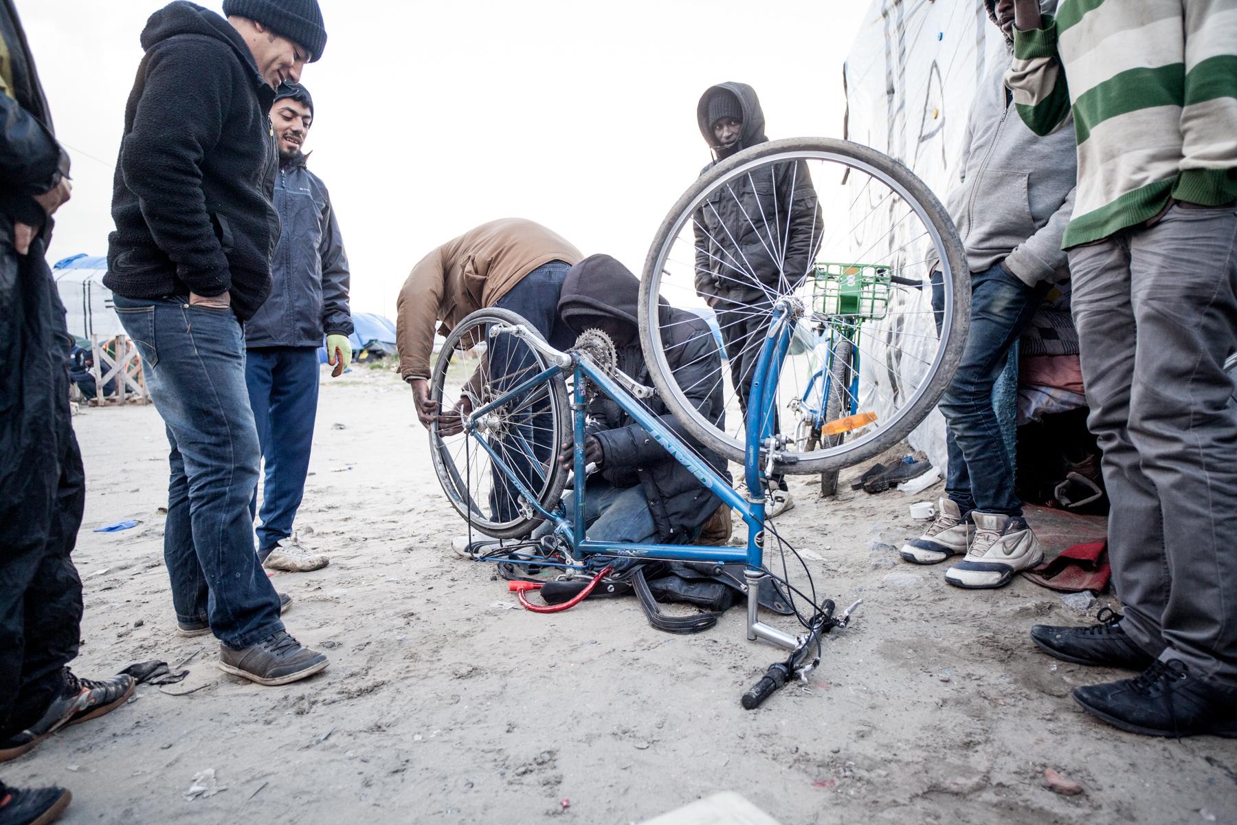 Dans la jungle, on utilise les sevices d'un autre migrant pour qu'il répare les vélos des autres.  Le Monde - 13.10.15