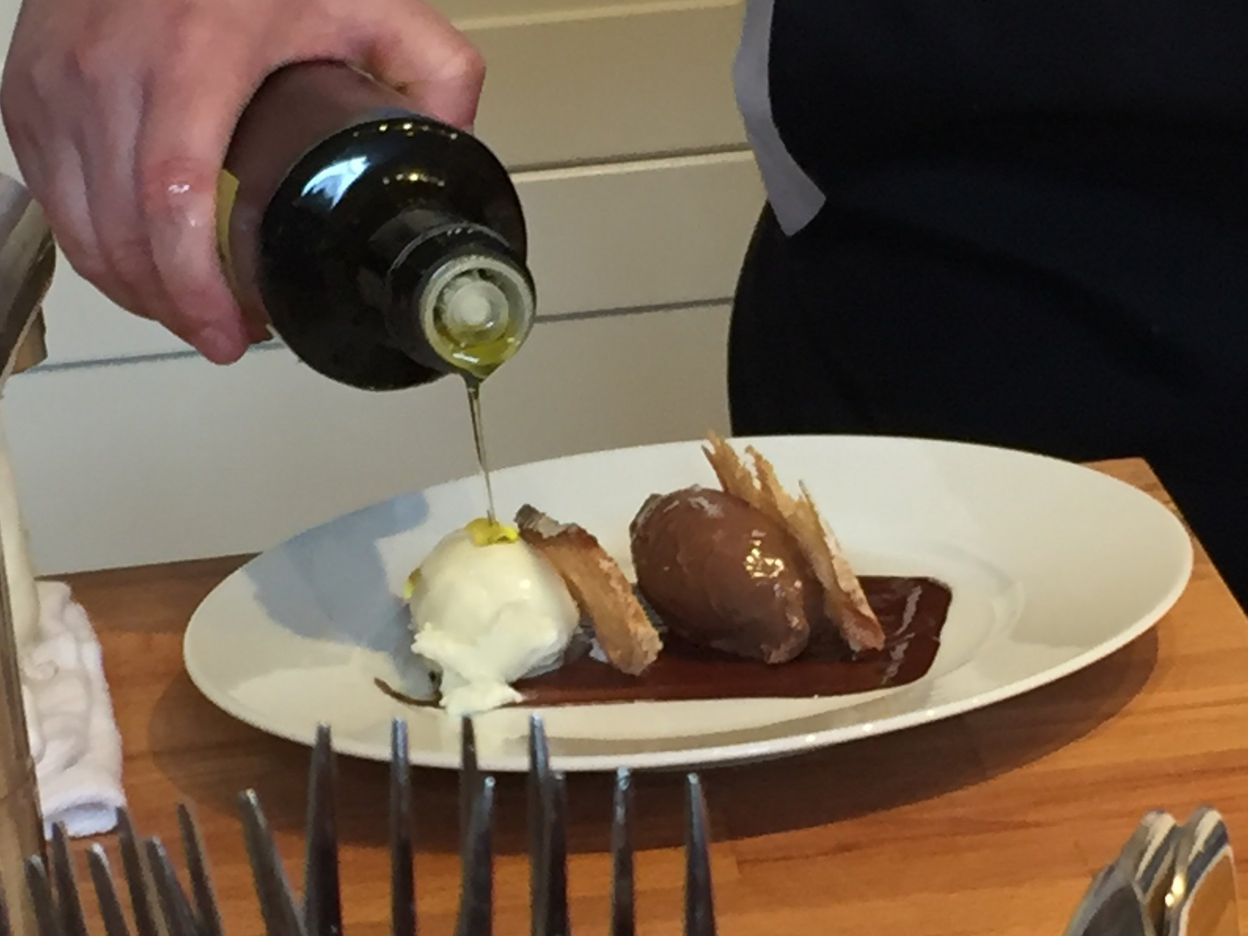 Heken Vass pours top quality Spanish olive oil onto her chocolate cremeux quenelle paired with an olive oil ice-cream and sourdough toast.