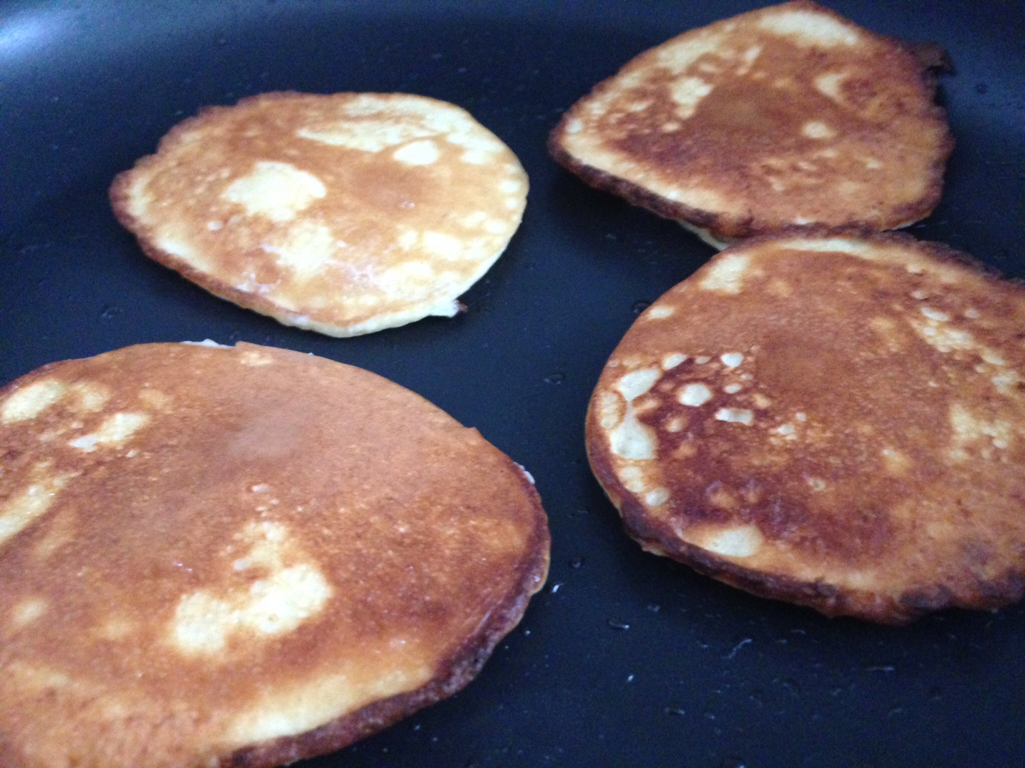 Pancakes frying in coconut oil.