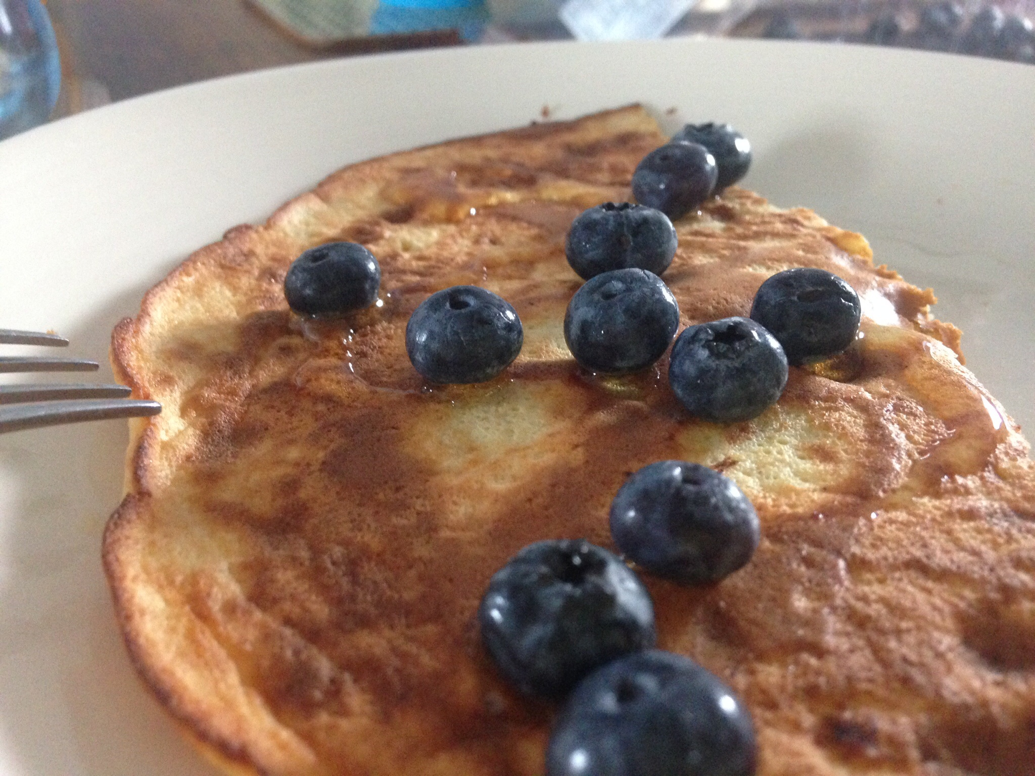Pancakes served with honey and blueberries.