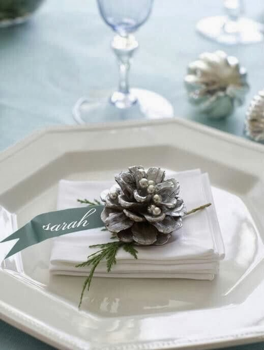A spray-painted pinecone and a sprig of conifer makes a beautiful place setting.