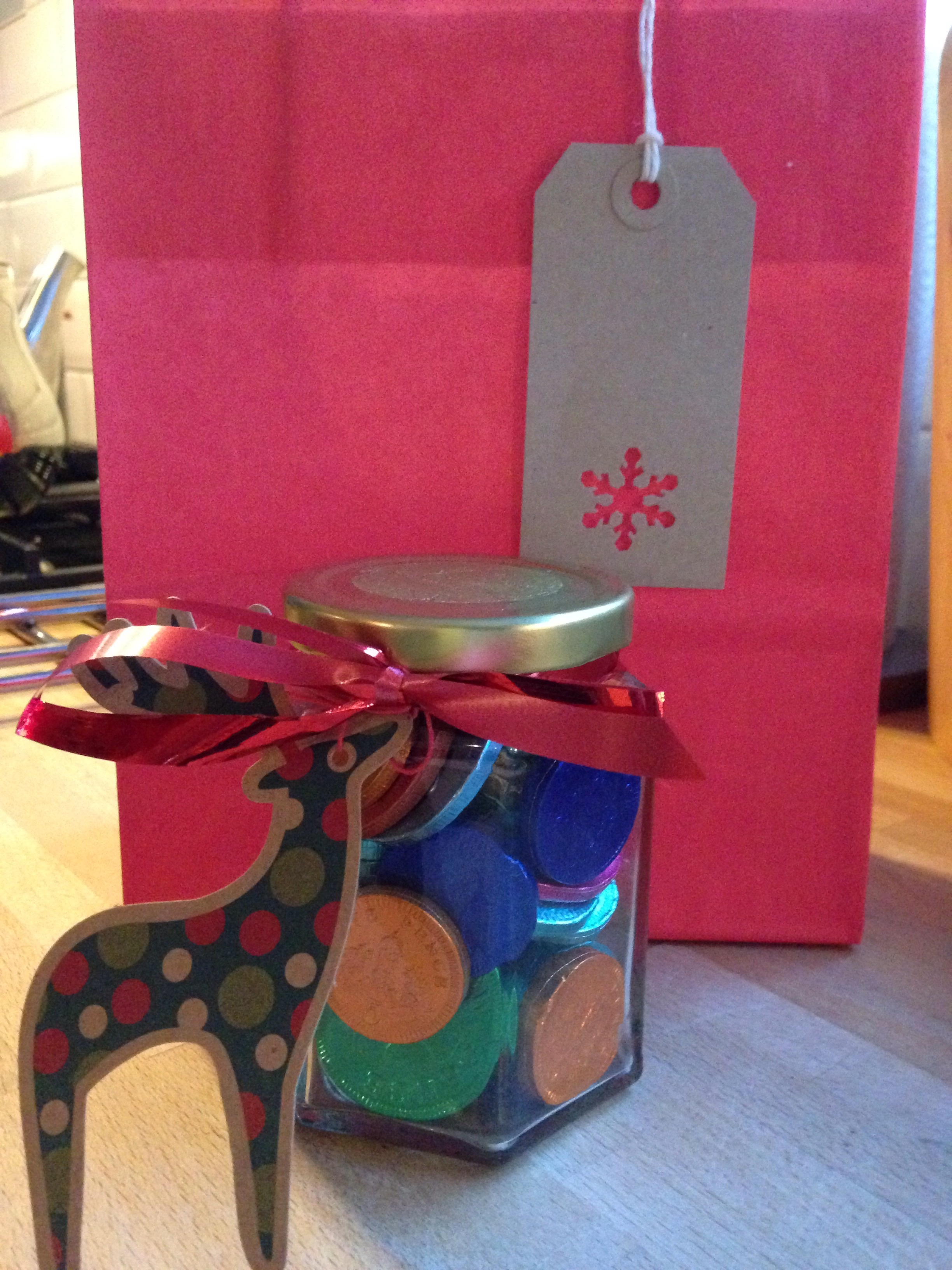 Chocolate coins in a jam jar, tied with ribbon & a Christmas tag.