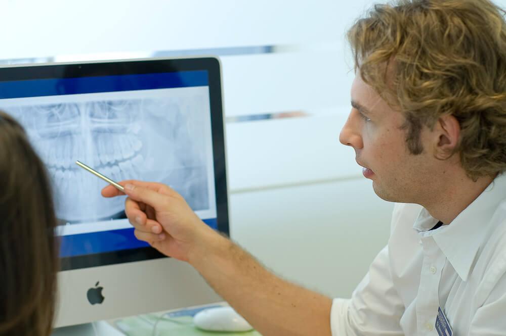 Konsultation einer Patientin durch Dr. med. dent. Alexander Dudic im separaten Beratungszimmer.