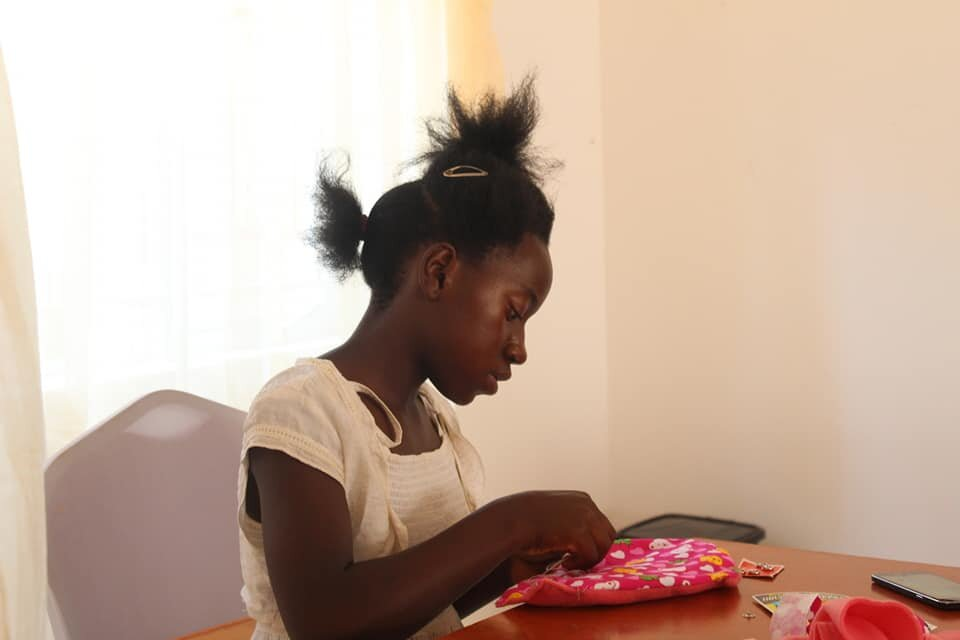 A young woman from the center makes her first reusable pad.