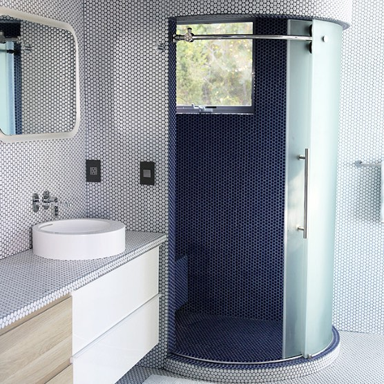 Mini honeycomb tiles covered the walls, showers and floors of each bathroom. We love the way is creates a spa-like feel at home.