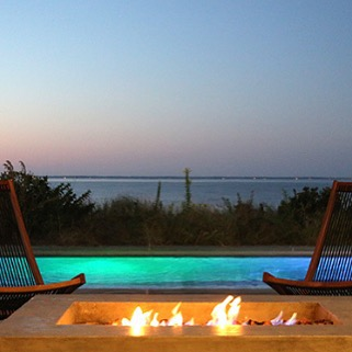 At night, the lap pool lights up, setting the mood for outdoor summer parties while the cement fire pit is perfect for chilly evenings.