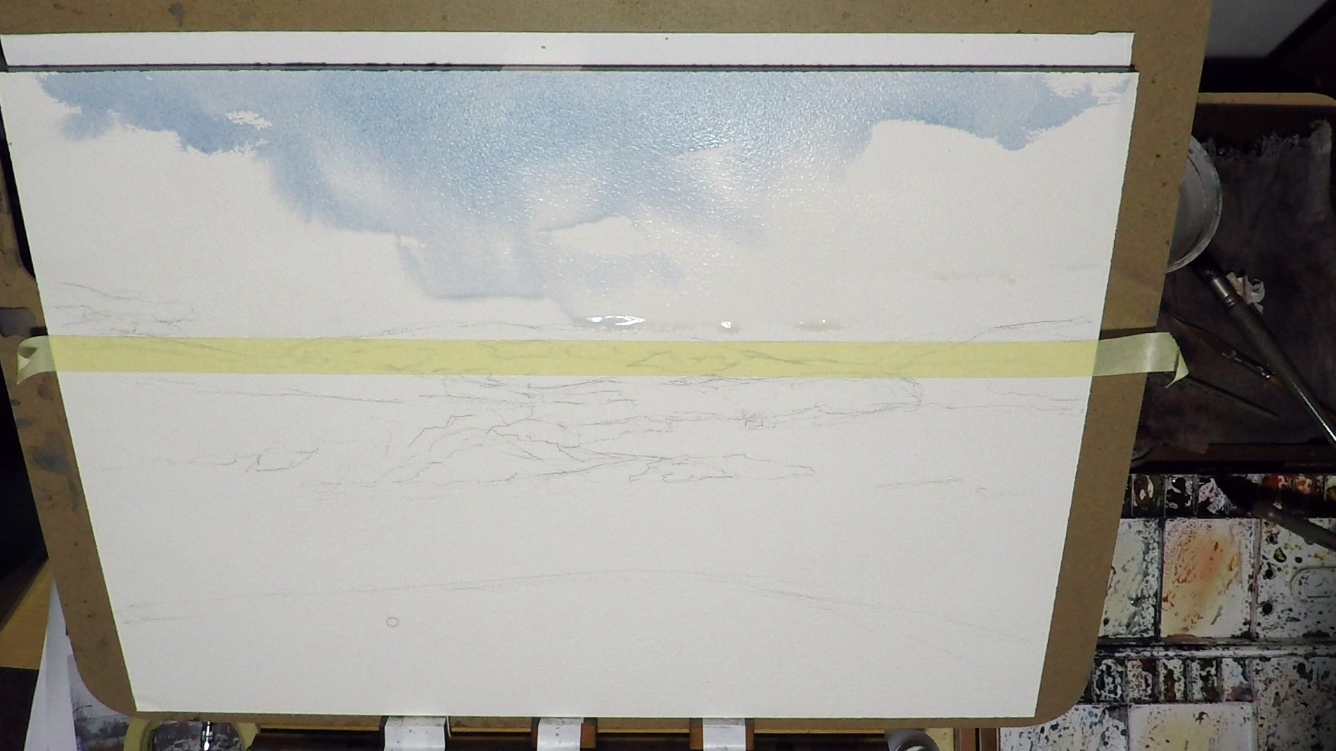 2. While it's still wet, I started to put in some Cobalt Blue, that will be the blue sky. Again I keep in mind the shape of the cloud. When the paint hits the wet area, it becomes a soft edge. When the paint hits the dry area, it'll be hard edge. Clouds are basically a mixture of hard and soft edge.