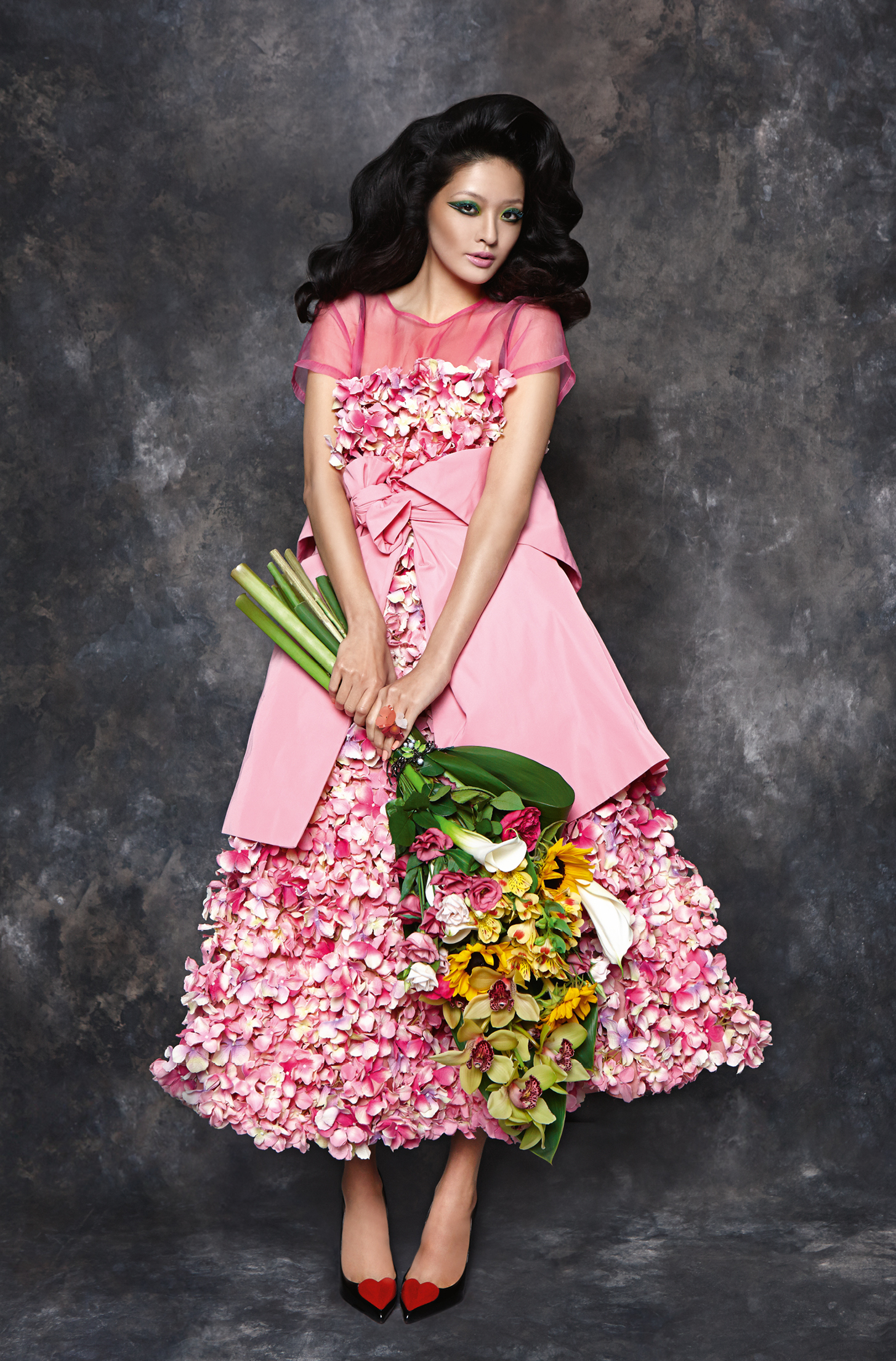 Flower dress,  Zeynep Kartel.  Pink coat (tied around waist),  Moschino   Cheap & Chic.  Pink sheer top,  2nd Day.  Sheer stockings,  Mrs Miller.  Flower ring,  Tatty Devine.  Black heart stilettos,  Christian Louboutin.  Bracelet (attached to flowers),  Mawi.
