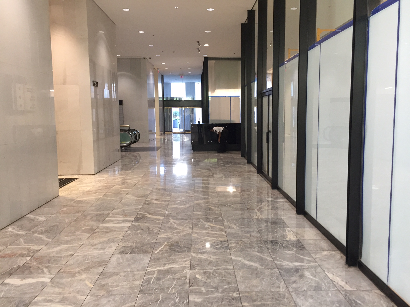 Enter an office building.  Walk towards the desk.