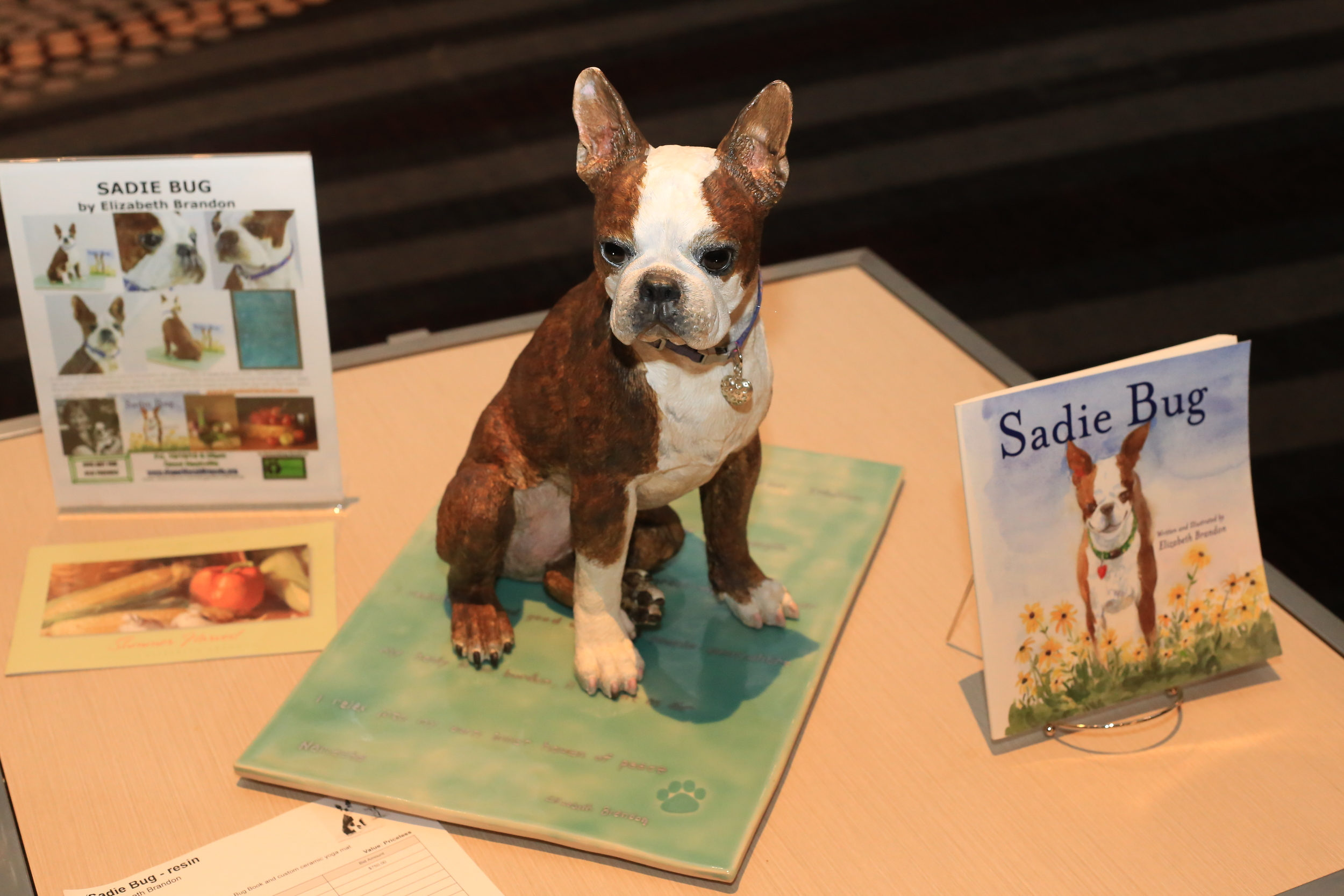 Sadie Bug statue on display with her ceramic yoga mat and children's book for the live auction.