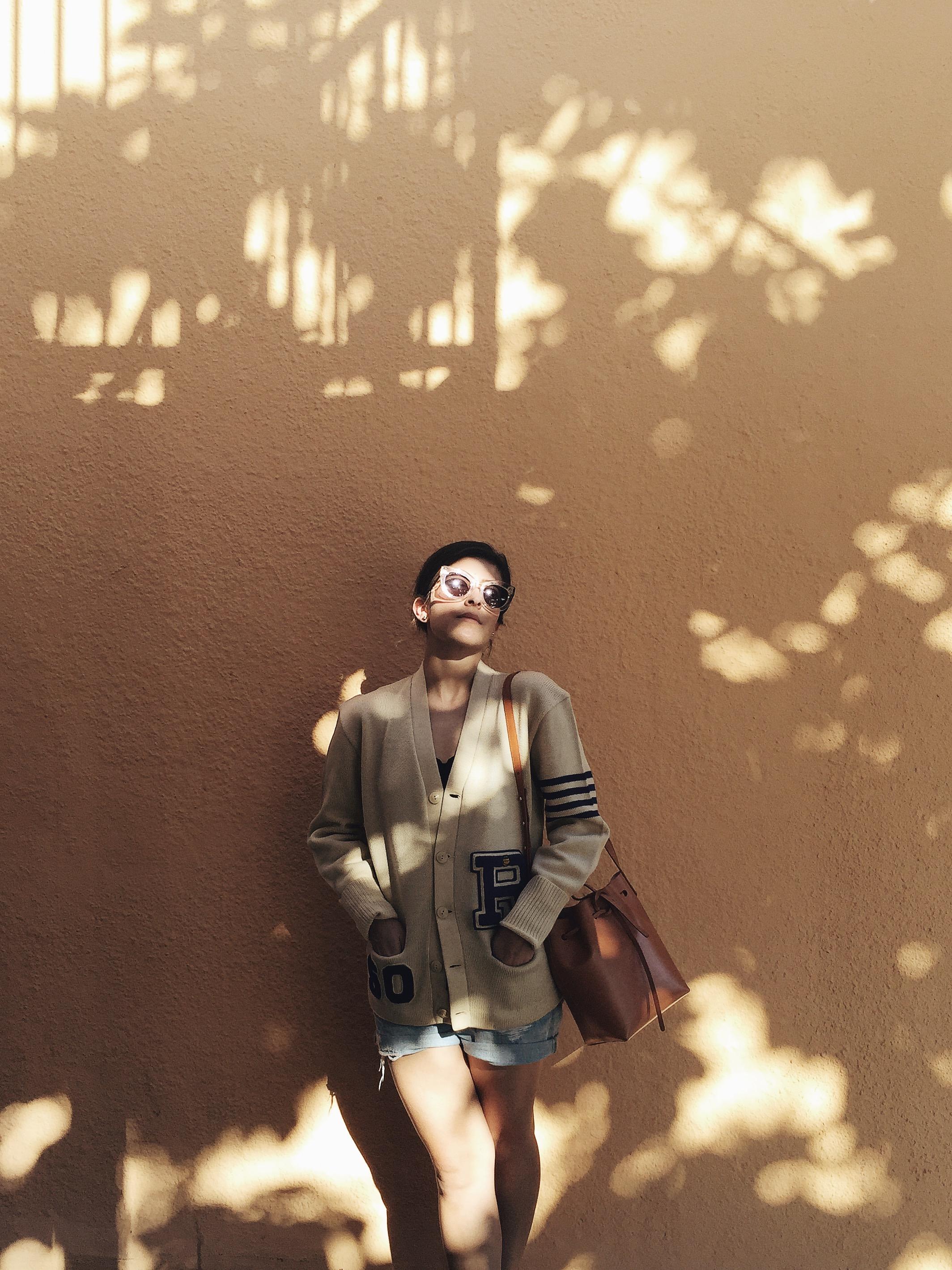 Céline Caty sunglasses in lucite, vintage letterman jacket, Mansur Gavriel mini bucket bag