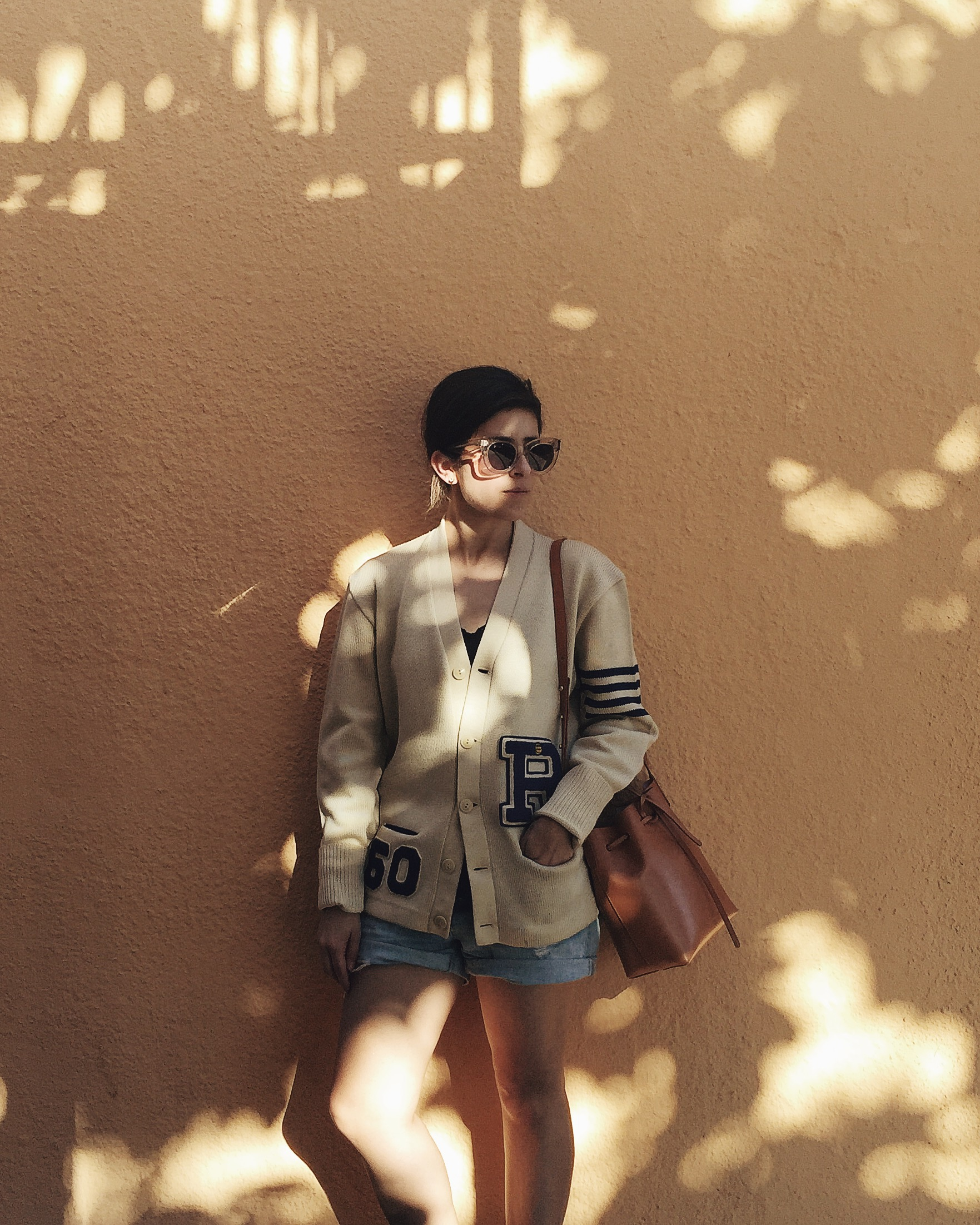 Céline Caty sunglasses in lucite, vintage letterman jacket, Mansur Gavriel mini bucket bag