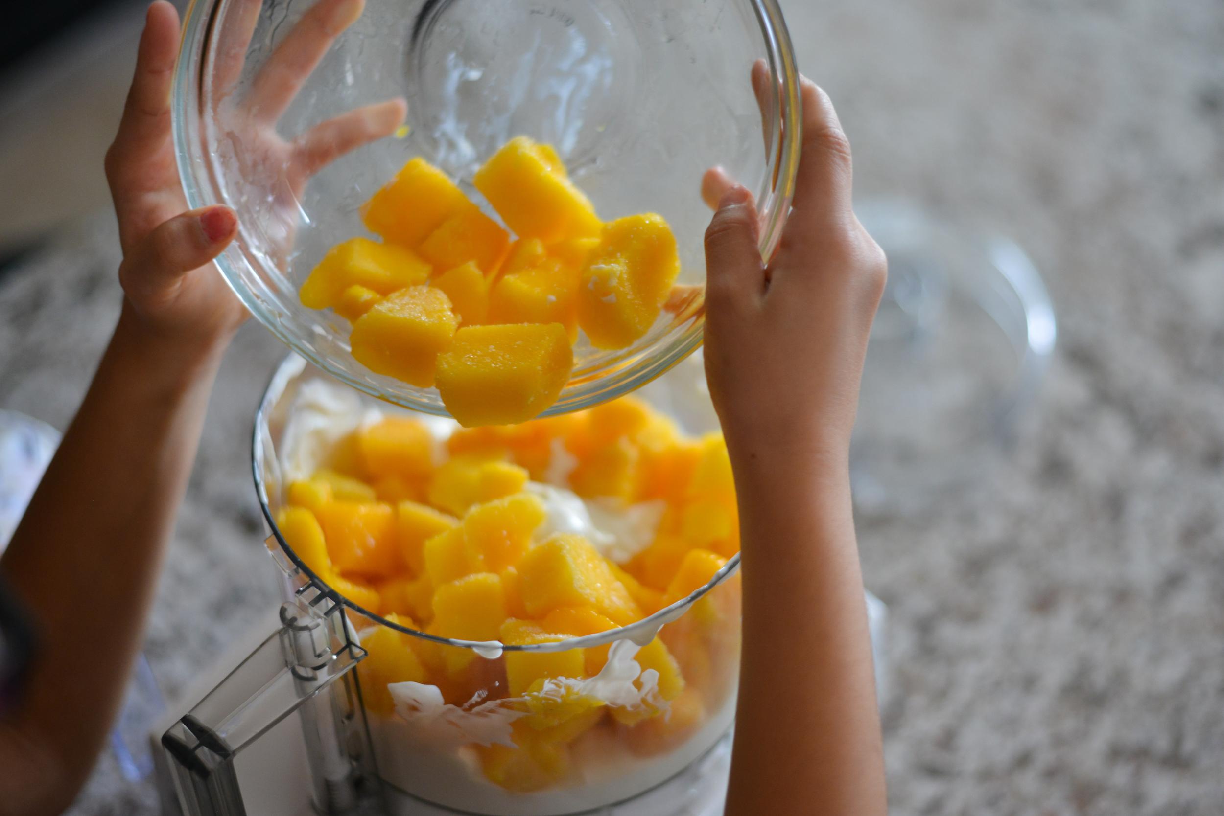 Pouring mango into processor