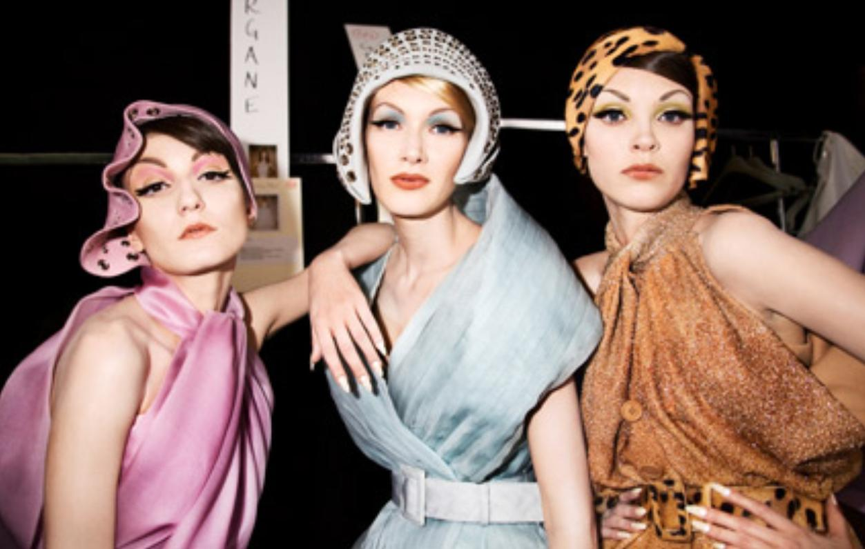 Three women dressed in art deco era fashions in brilliant but different colors