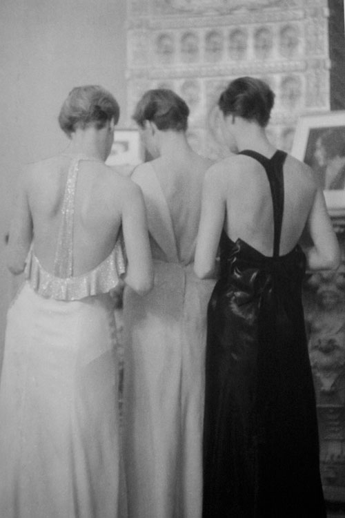 Three women standing showing the backs of their art deco era gowns