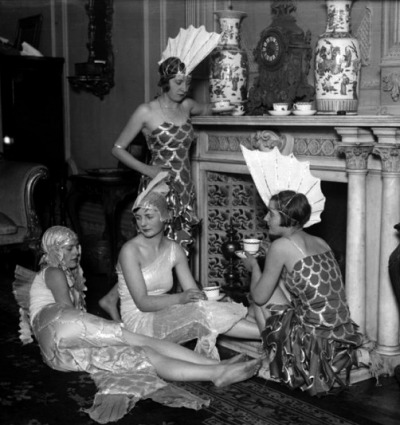 1920s art deco era women in mermaid costumes sitting around a fireplace