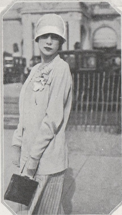 An art deco era woman on the street in 1920s daywear