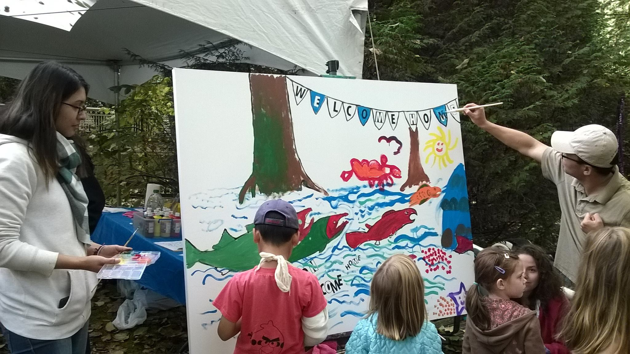 Children paint a mural with the Coquitlam River Watershed Roundtable to welcome home the salmon.