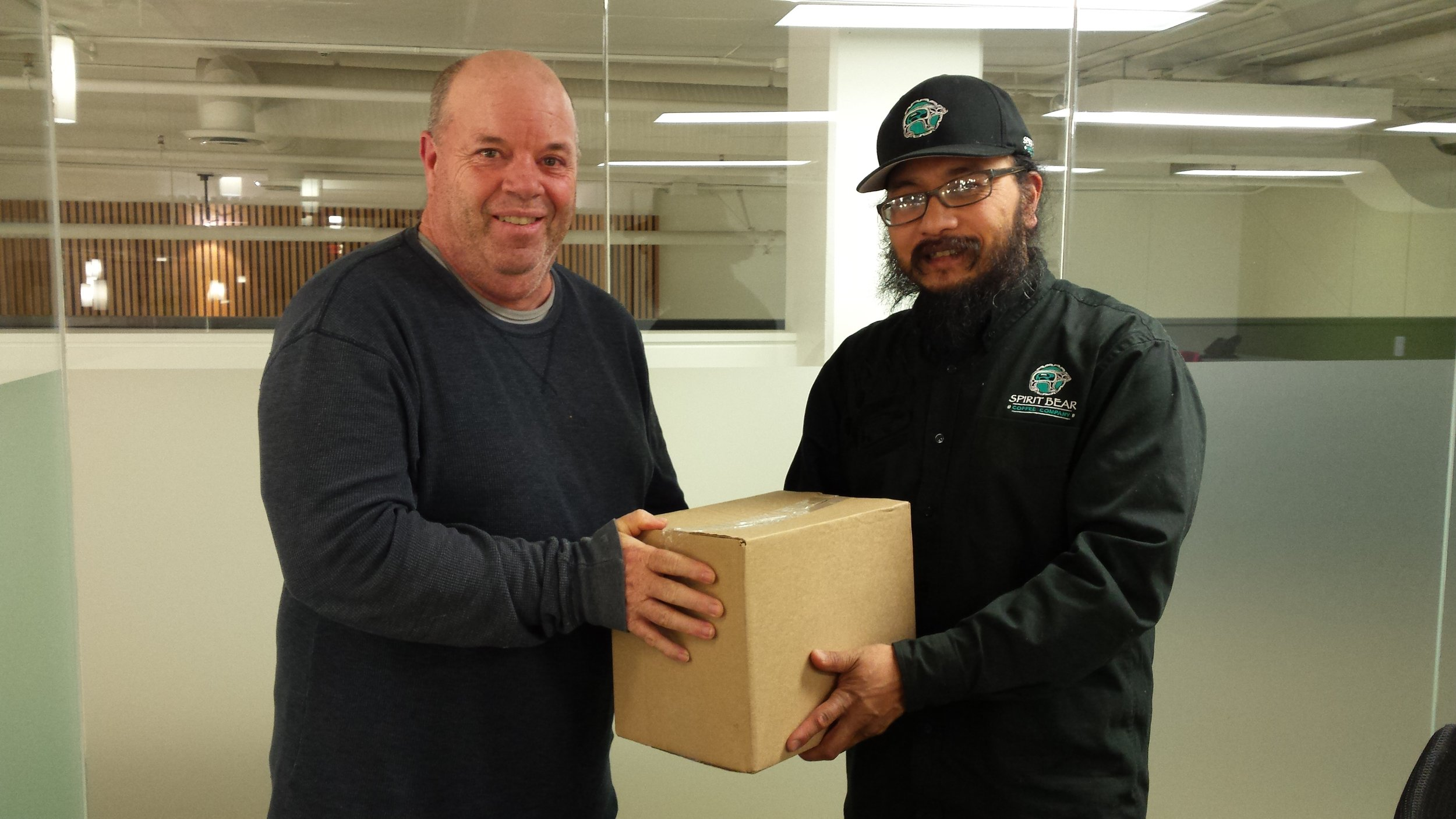 Stewart Brotchie receives a box of Spirit Bear coffee from Jay Peachy after a presentation by Jay at our recent meeting