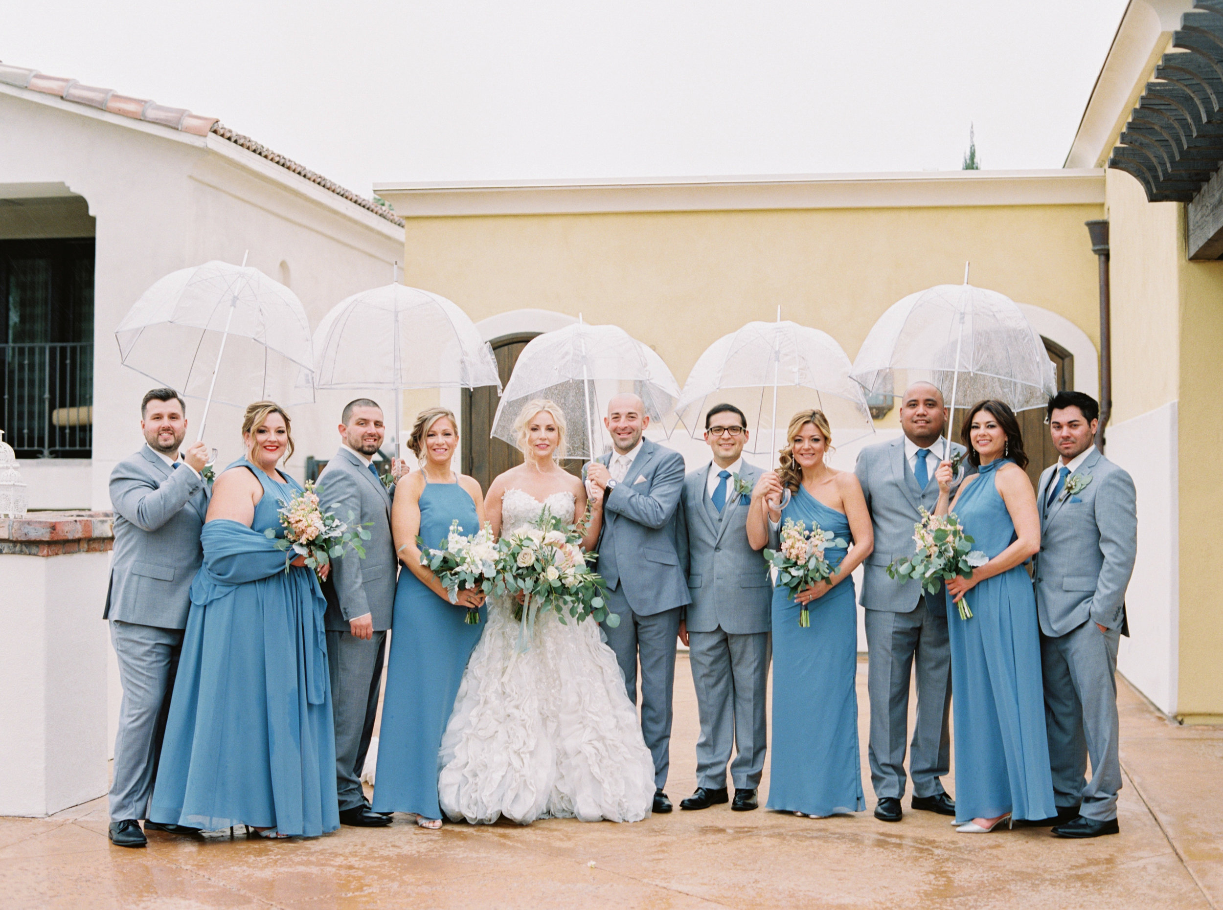 22 wedding party bridesmaid groomsman custom grey suit blue bridesmaid dress clear umbrella rain on wedding day rain during wedding pictures cloudy wedding day Life Design Events photos by Melissa Jill Photography.jpg