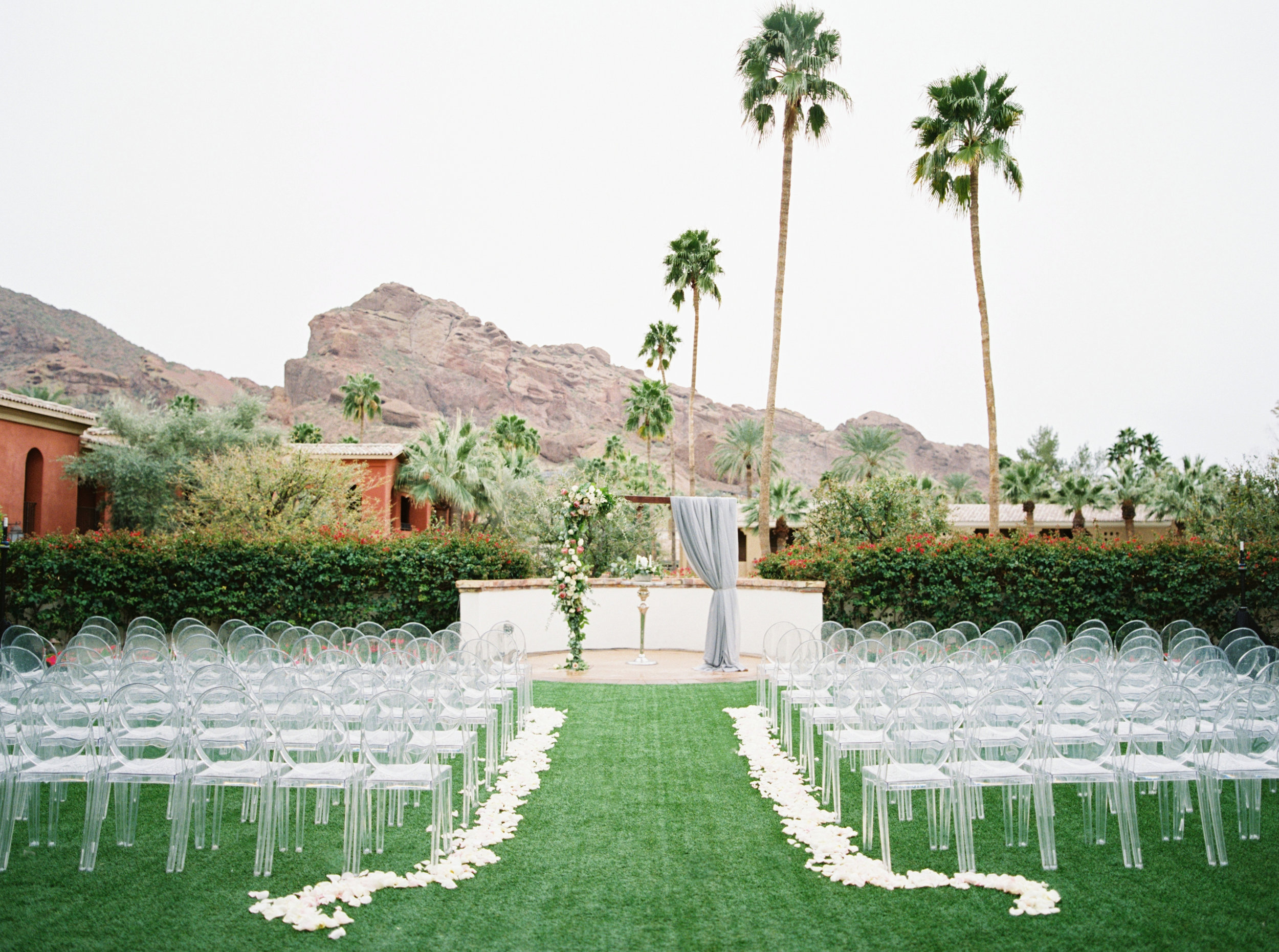 27 ceremony seating ghost chair flower aisle ceremony arch floral arch omni scottsdale montelucia wedding outdoor wedding rainy wedding rain on wedding day Life Design Events photos by Melissa Jill Photography.jpg